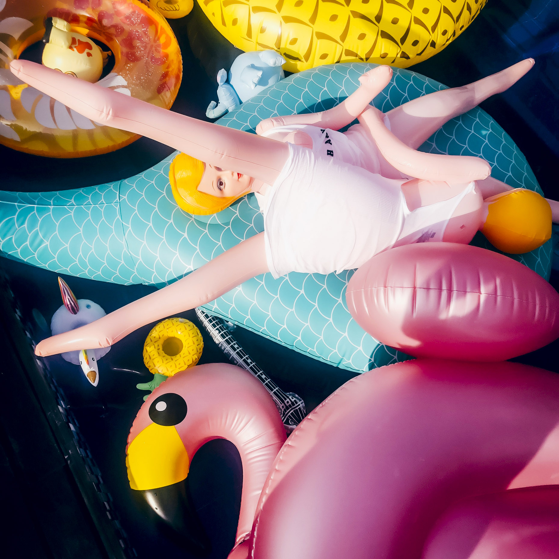 Overhead shot of after the pool party with mix of pool floaties and blow up dolls