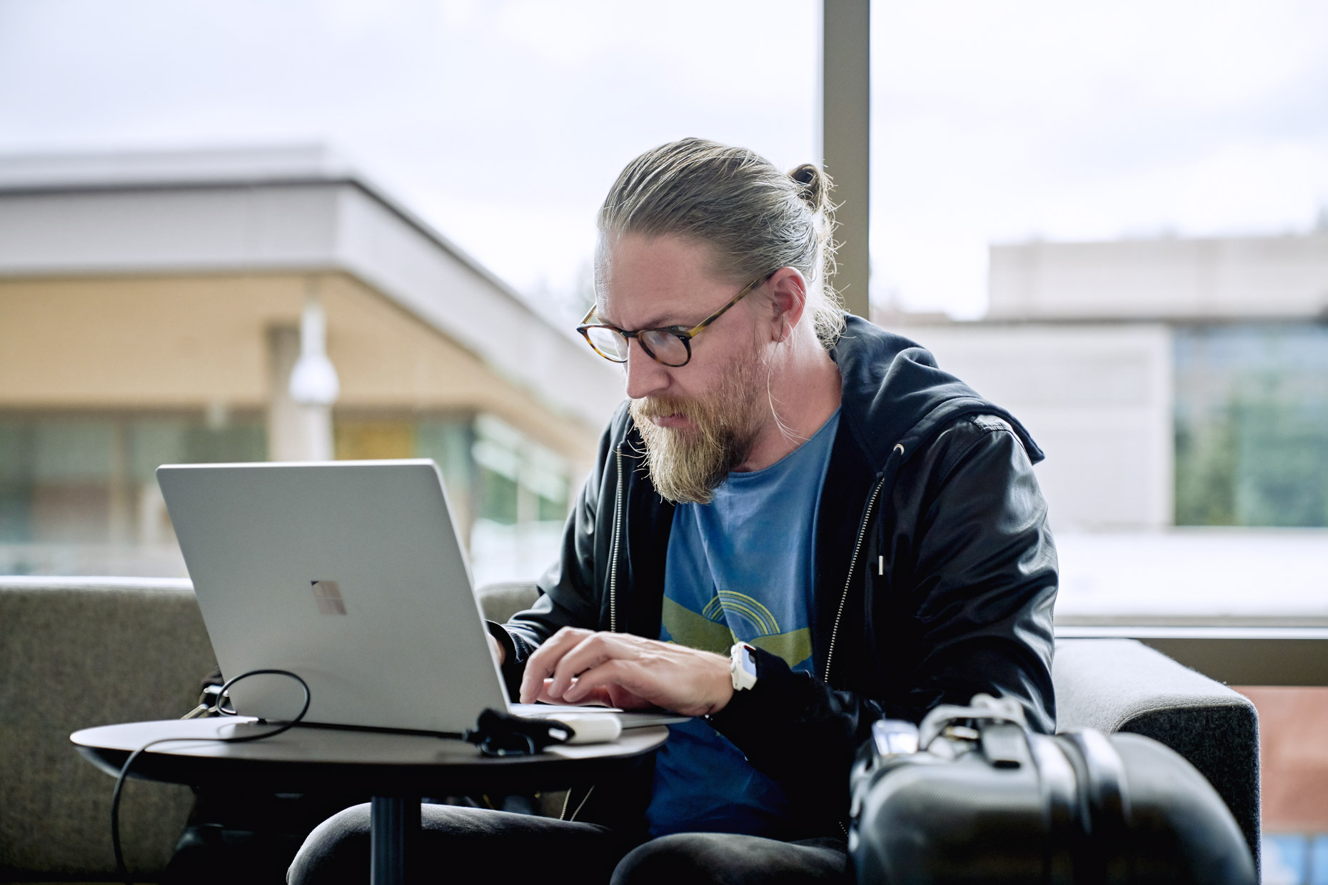Bearded man working on laptop in airport