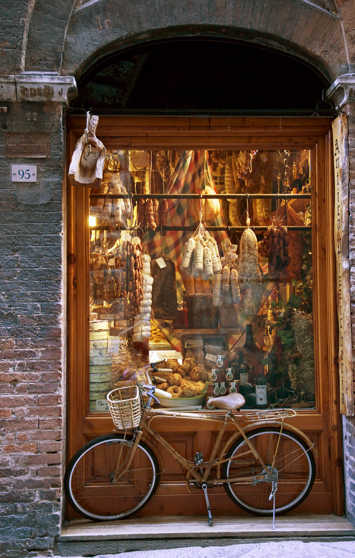 Bicycle in front of butcher food shop food in Siena Italy