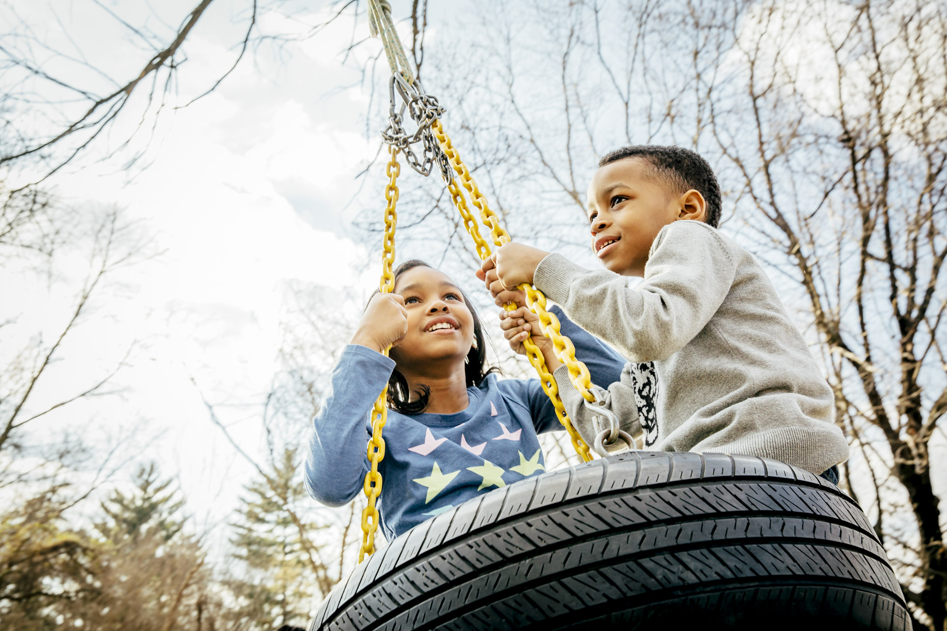 Black boy and girl swinging on tire swing in fall