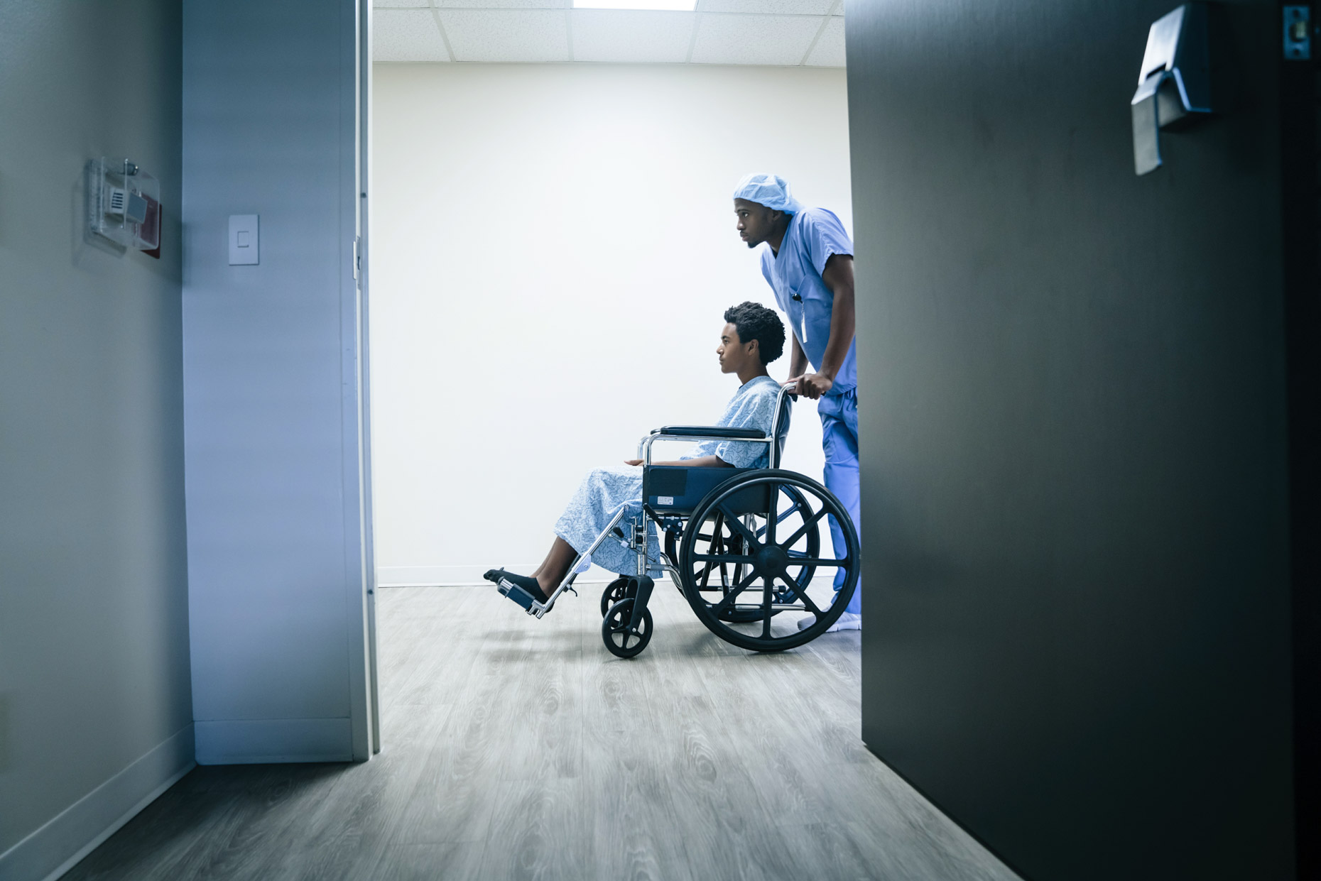 Black male nurse wheeling teen in wheel chair through hospital