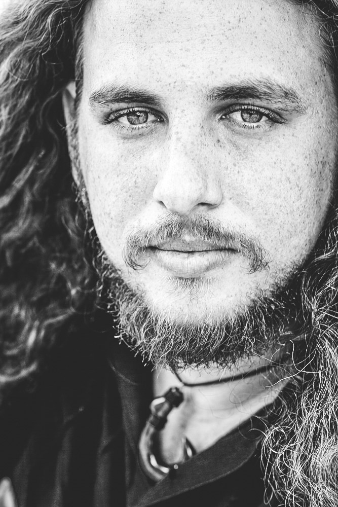 Black and white portrait of man with beard freckles and long hair