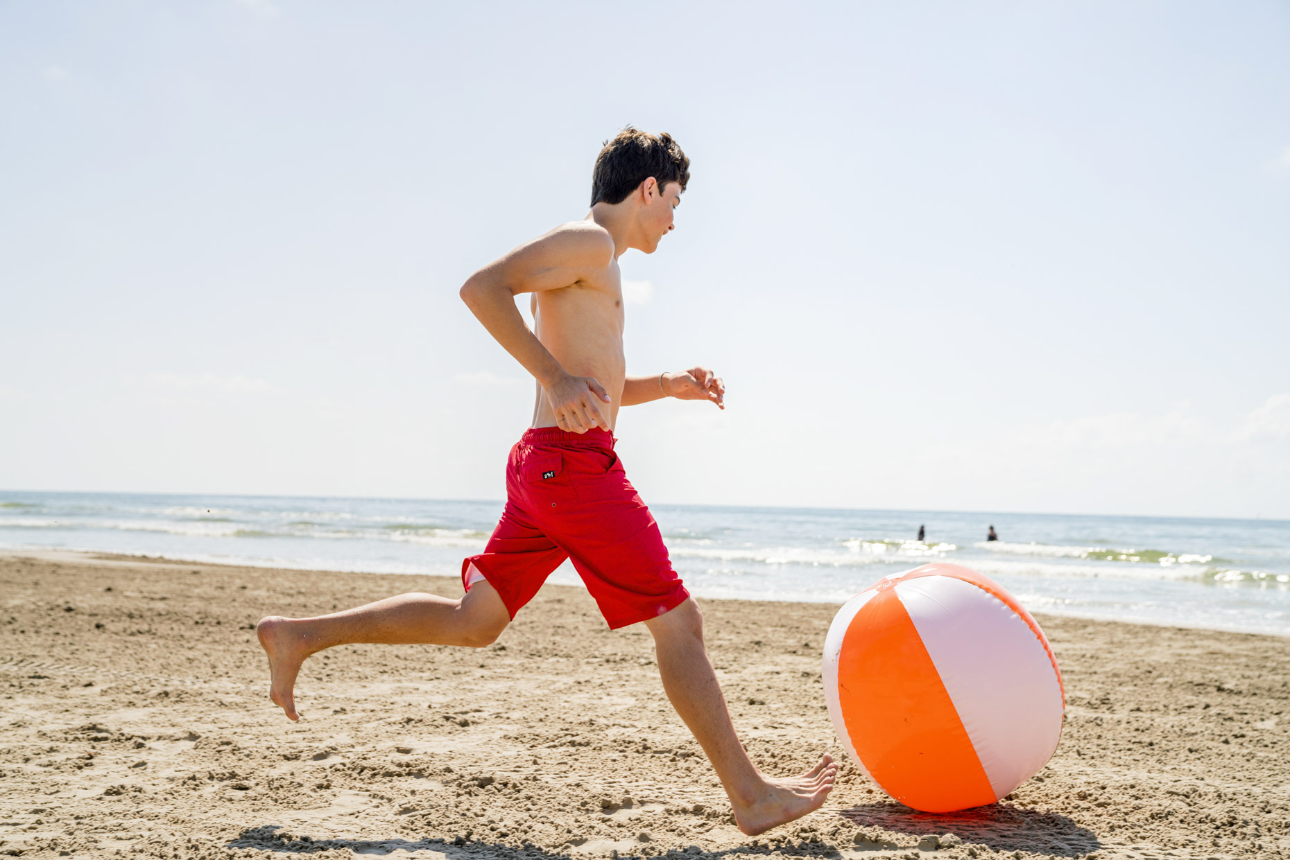 Boy kicking beach ball toward ocean