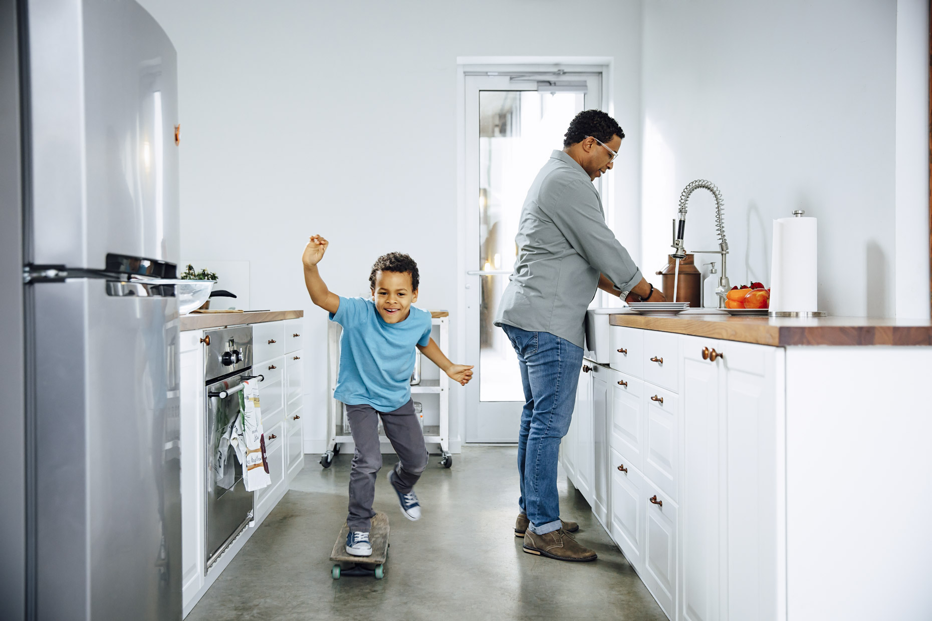 Boy skateboarding in kitchen while man does dishes