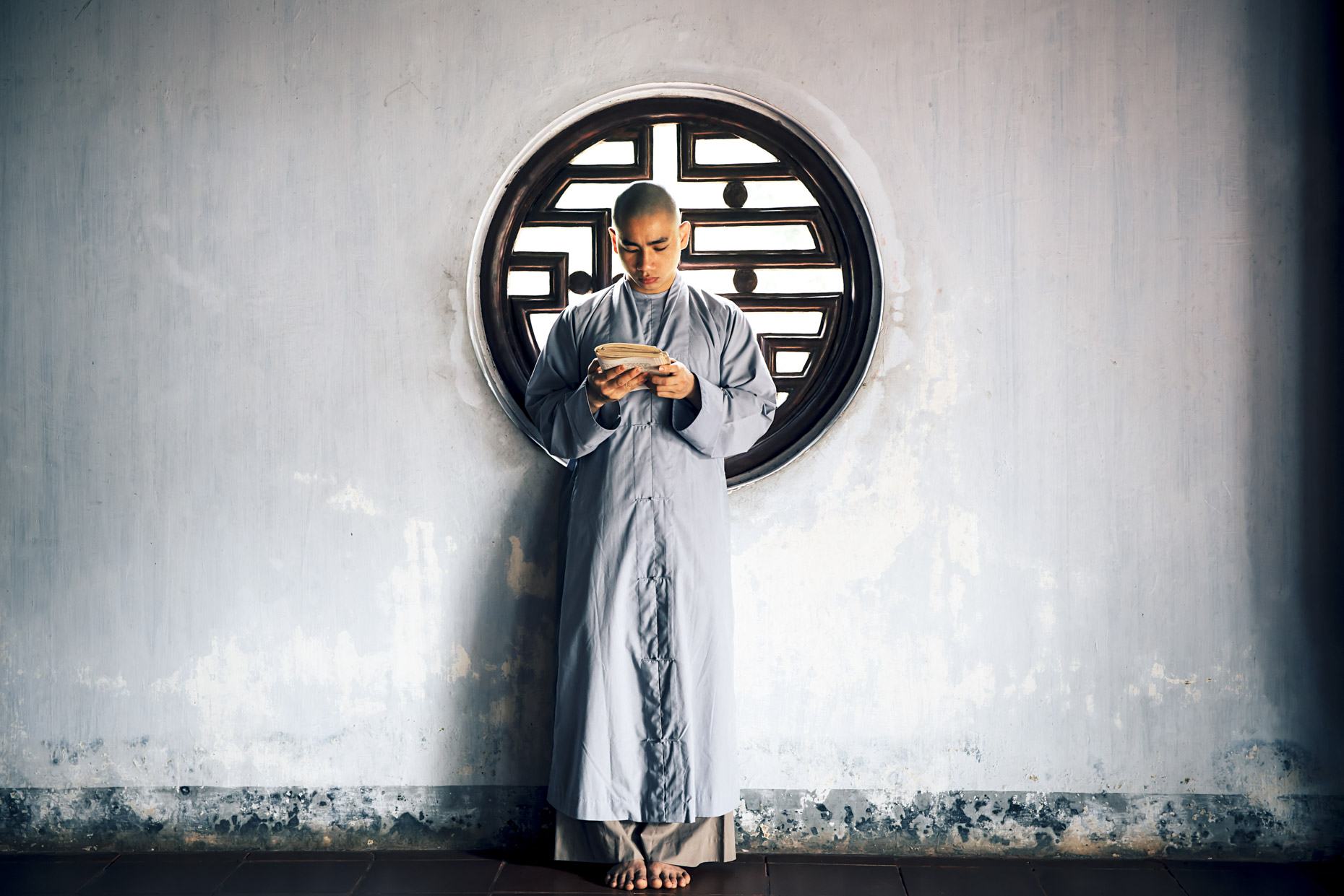 Buddhist Monk standing and reading in Vietnam
