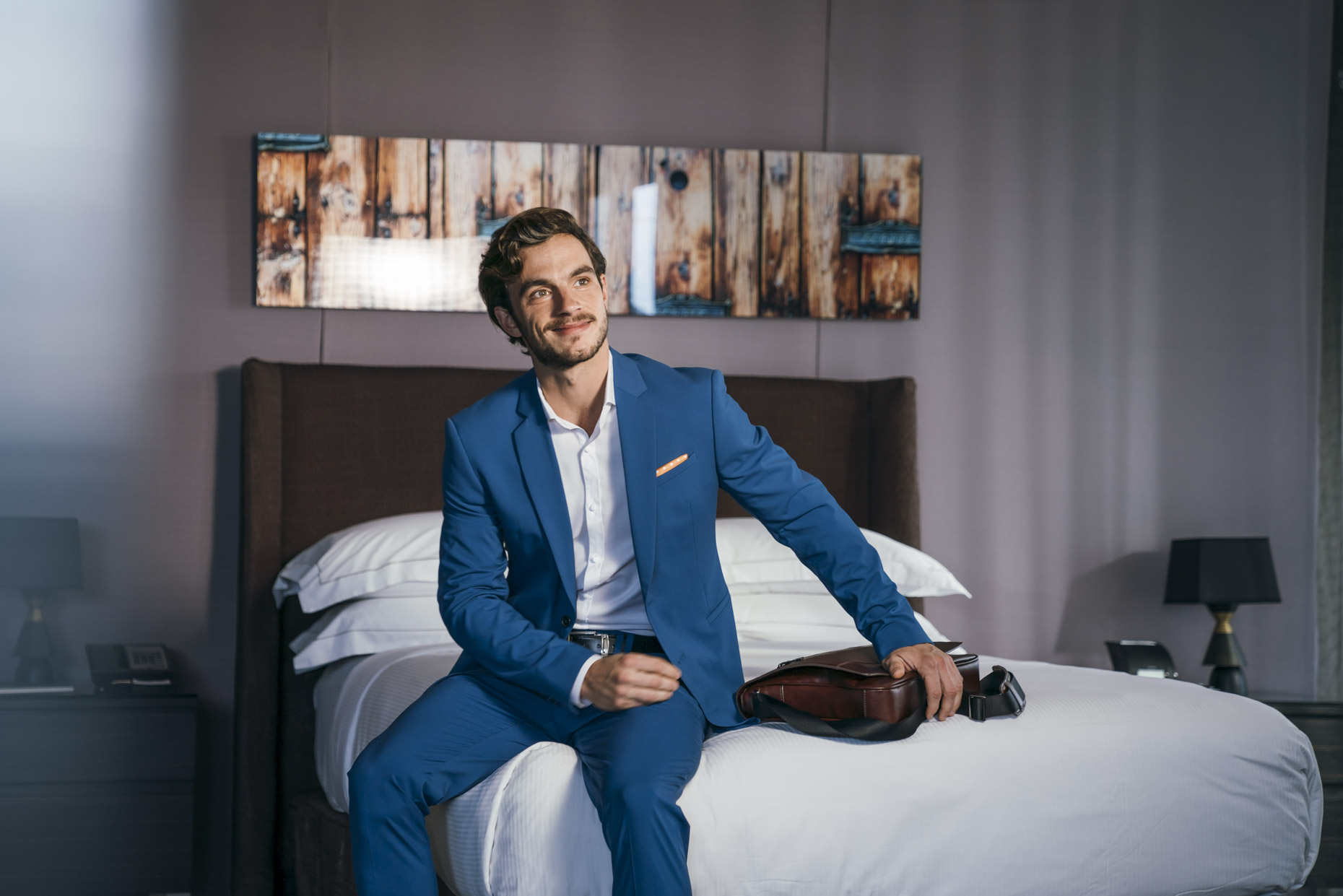 Business man sitting on bed in Hilton hotel with briefcase