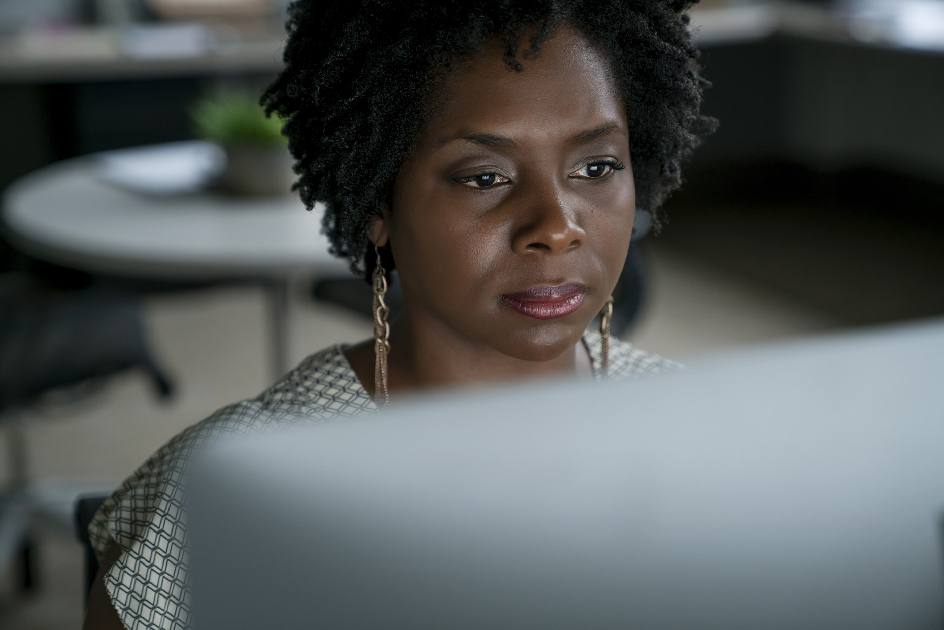 Close up of black woman looking at computer screen in the dark