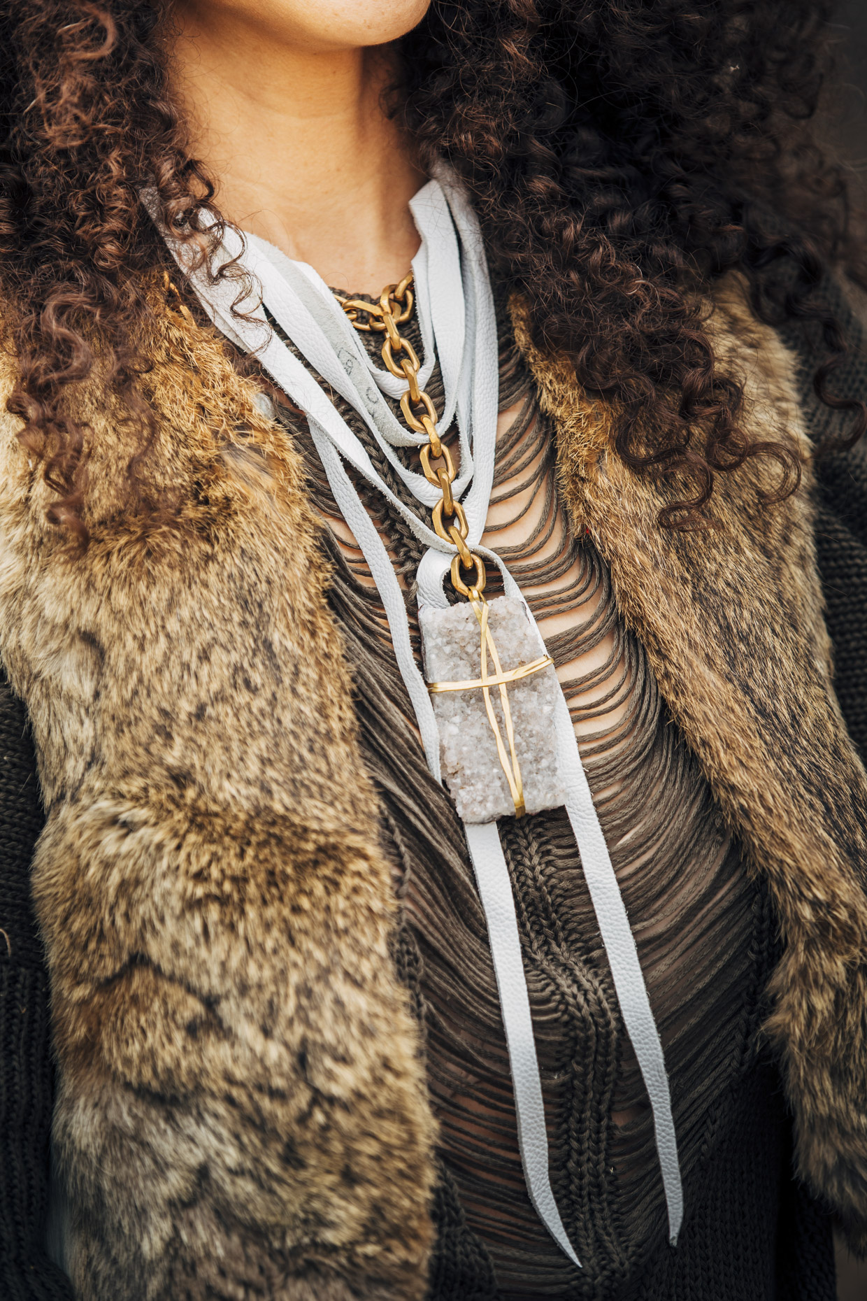 Close up of woman in fur vest wearing Belthazzar stone and leather necklace