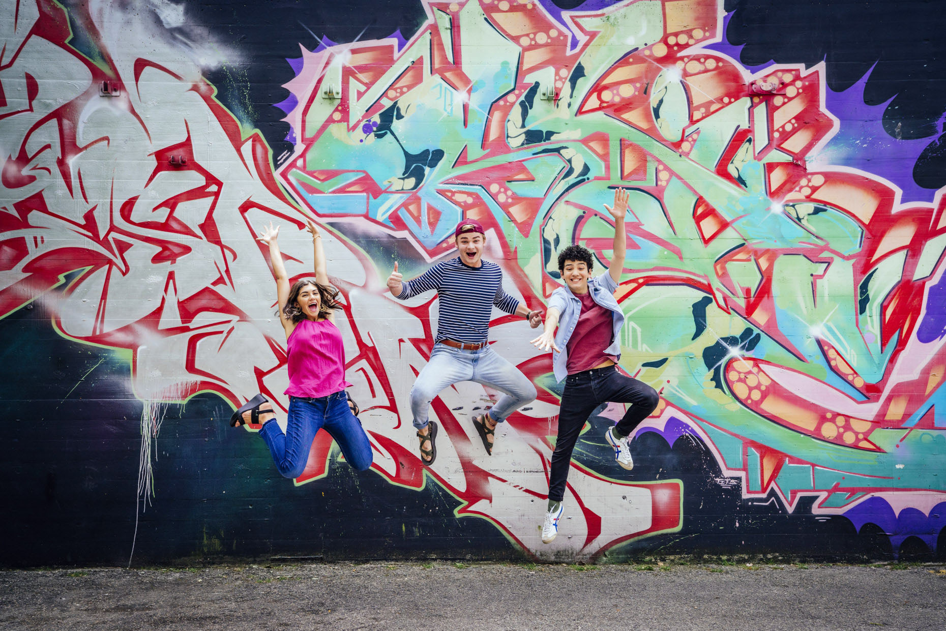 College students jumping in front of grafitti wall