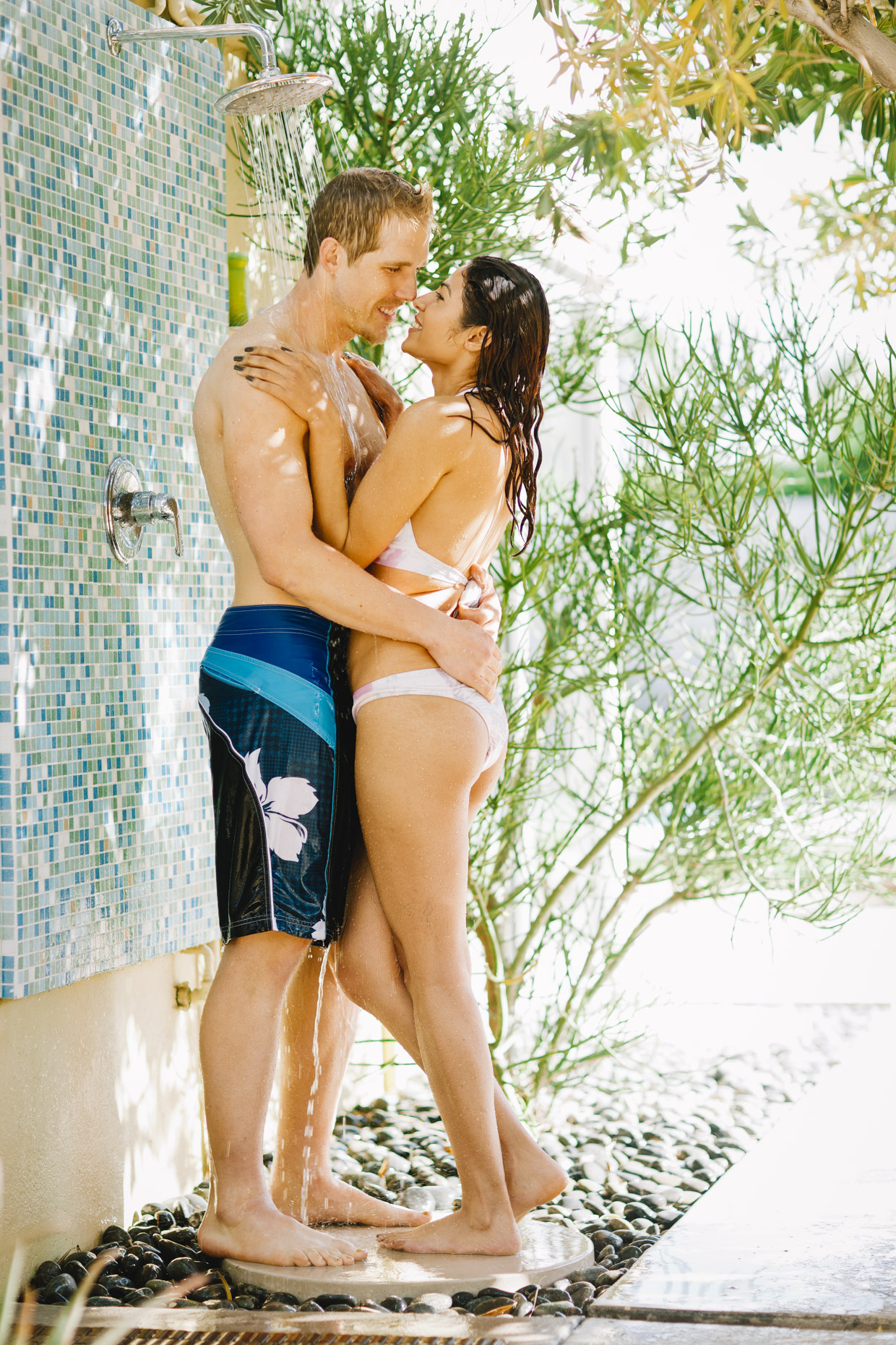 Happy Couple in swimsuits embracing under outdoor shower