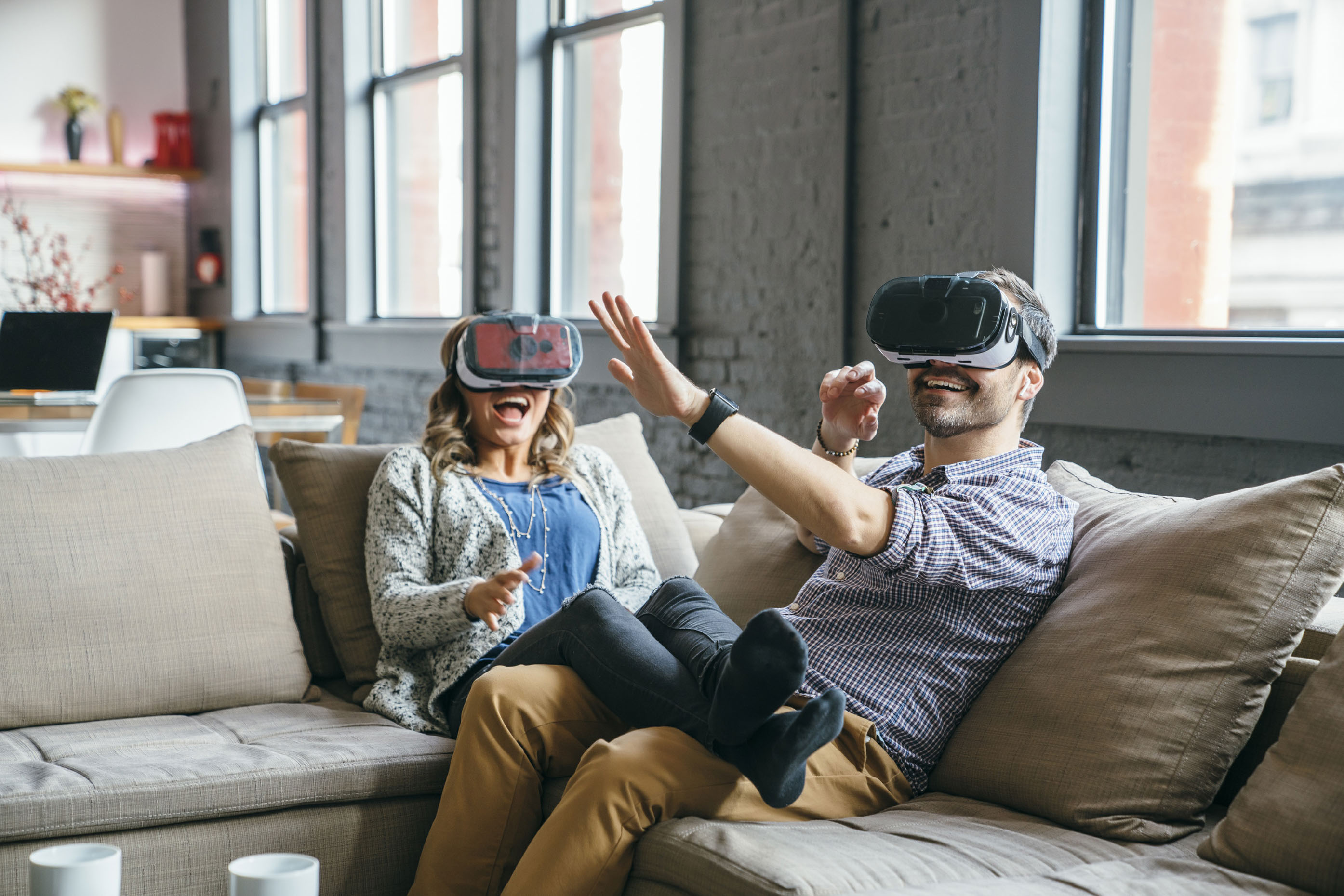 Couple-virtual-reality-glasses-on-couch-laughing-Inti-St-Clair-LYDA_201612133331