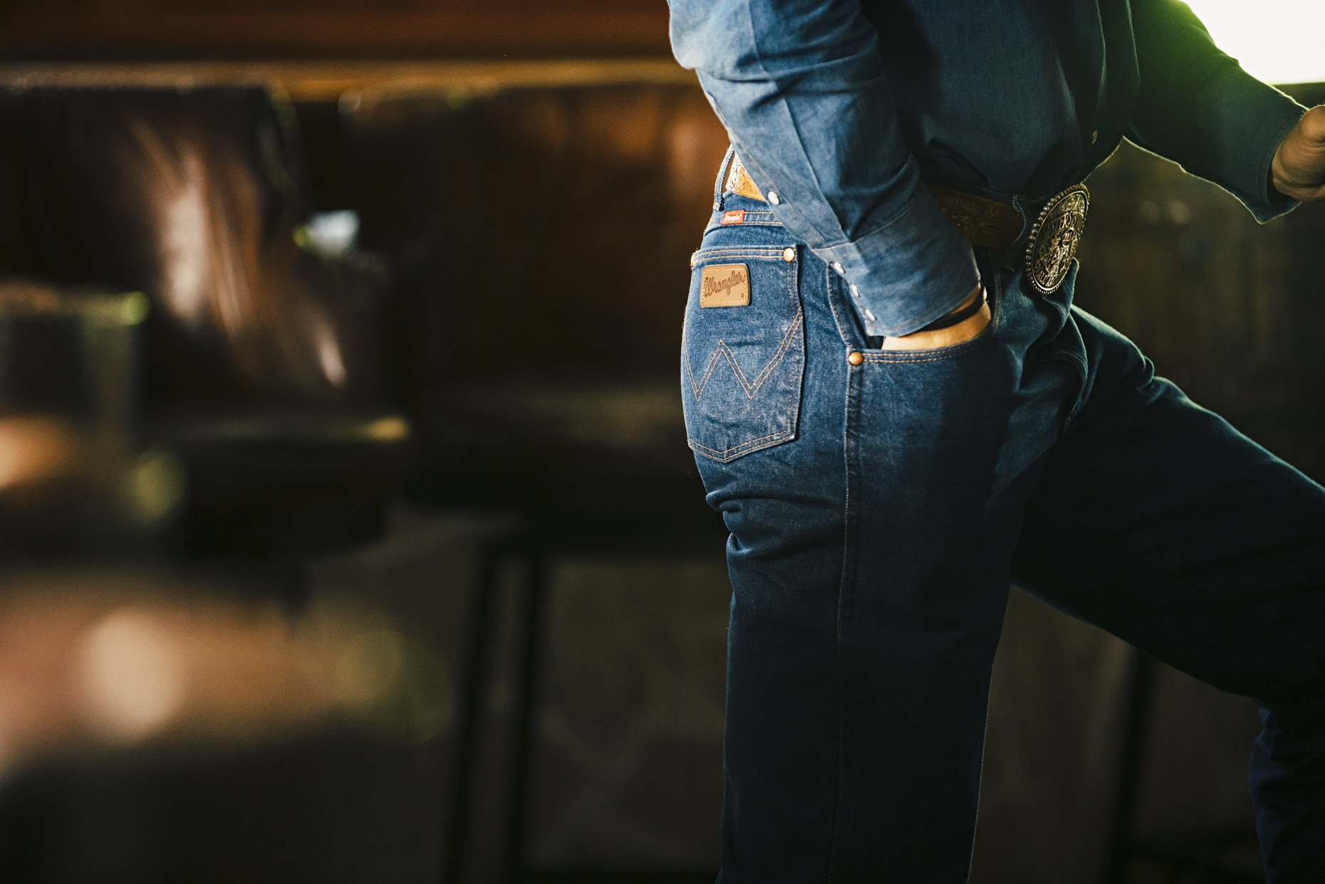Inti St Clair photo of tight shot of cowboy butt in wrangler jeans in bar