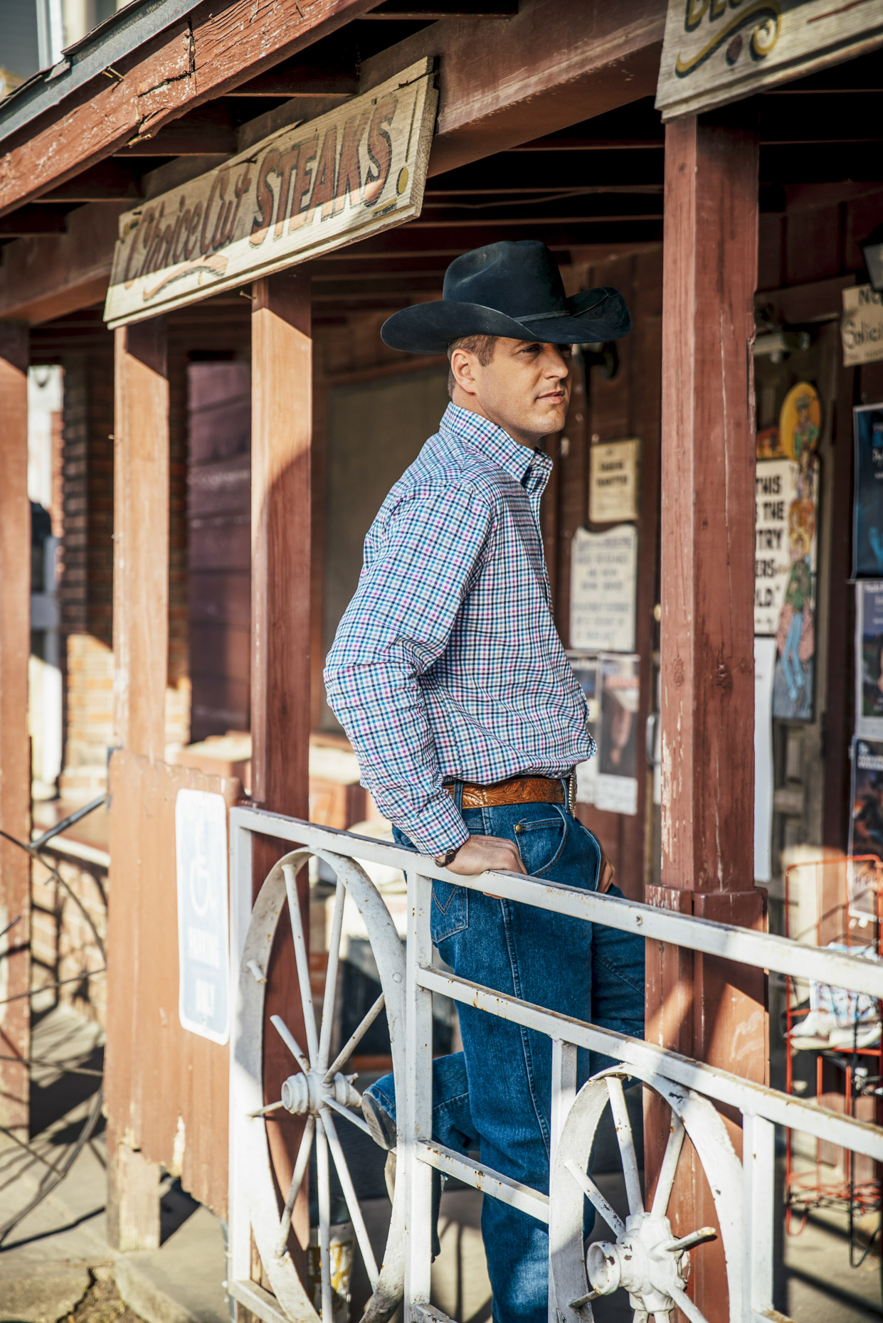 Cowboy in wrangler clothes and hat standing on porch of Broken Spoke bar