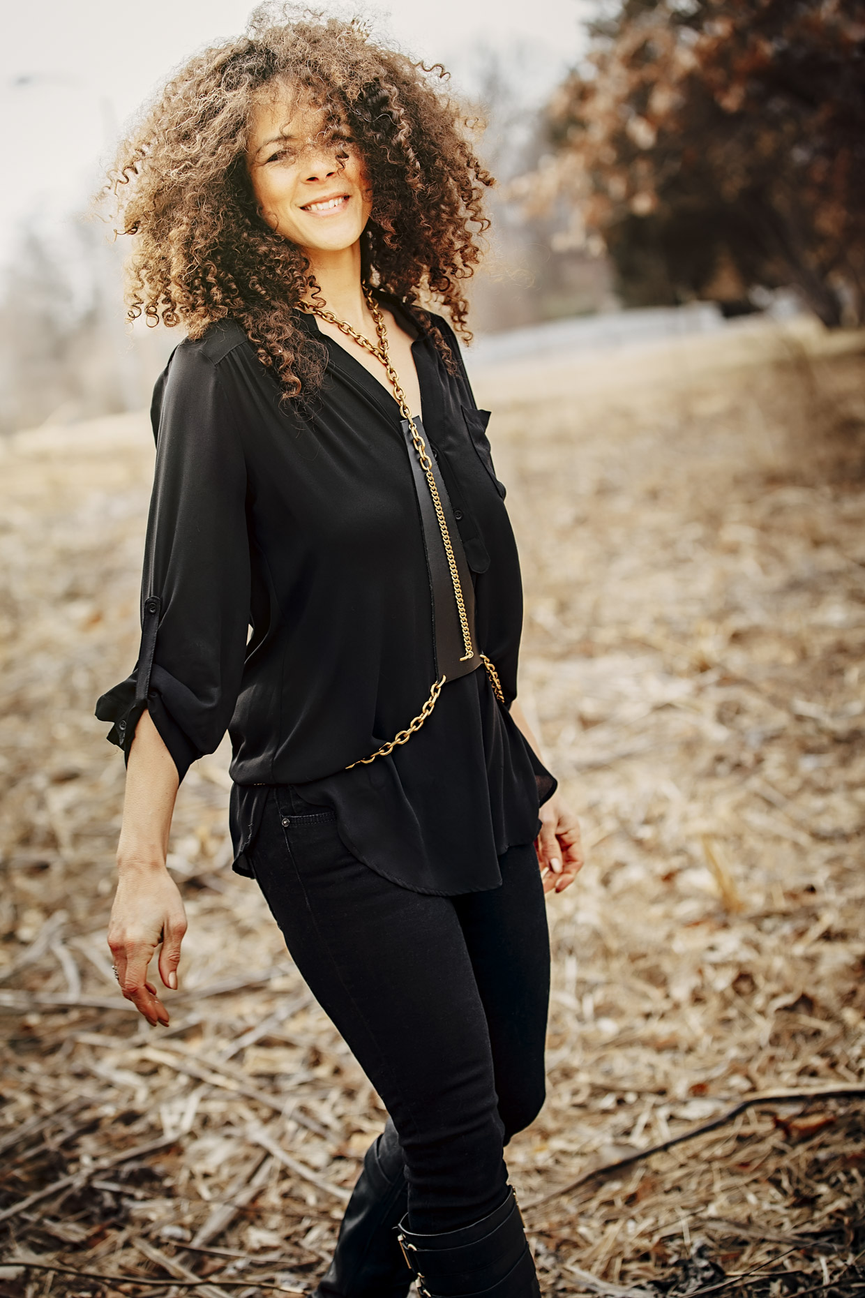 Curly haired woman in all black with Belthazzar Jewels brass and leather harness