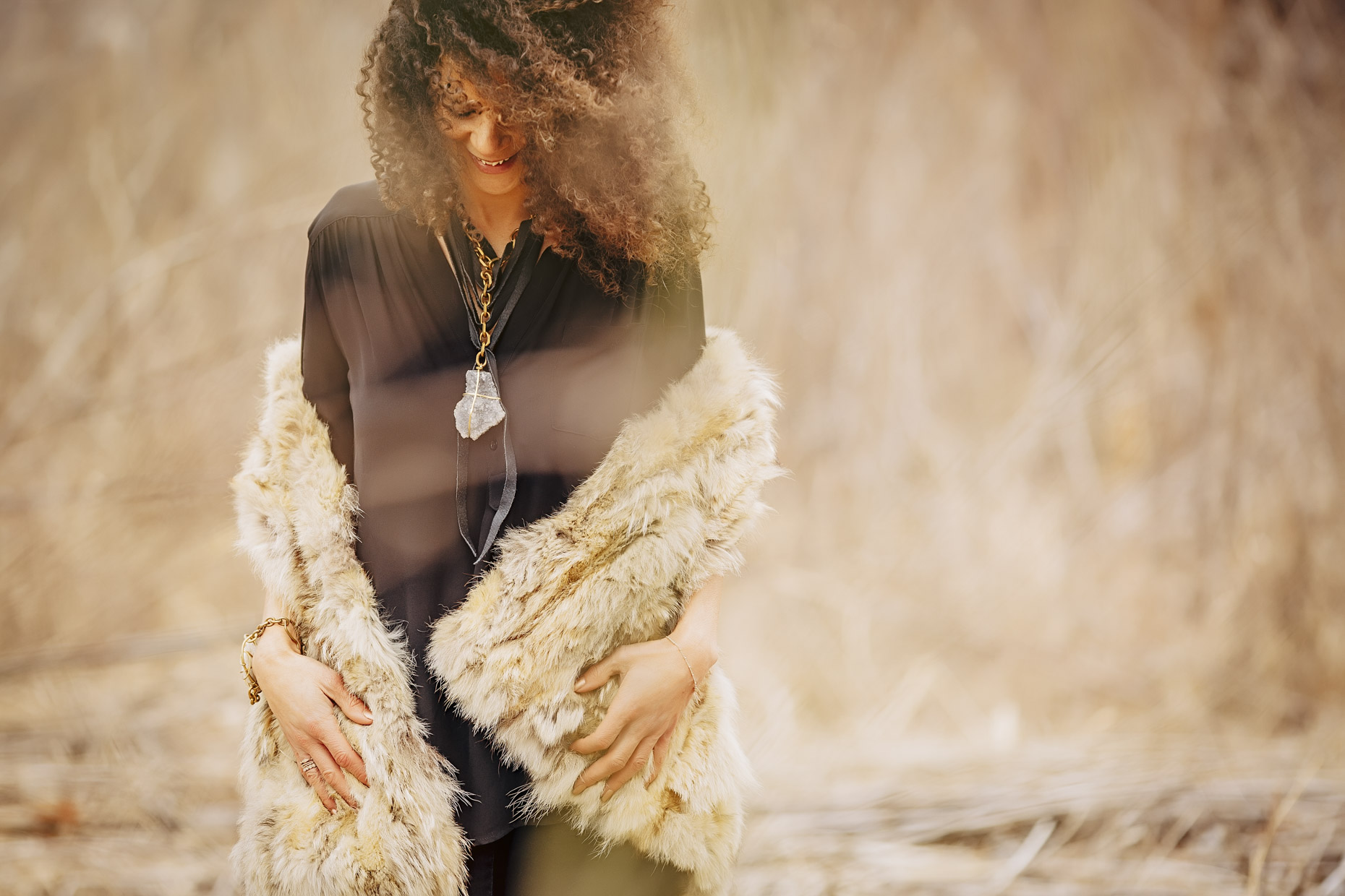 Curly haired woman in black with fur coat wearing Belthazzar Jewels brass stone necklace