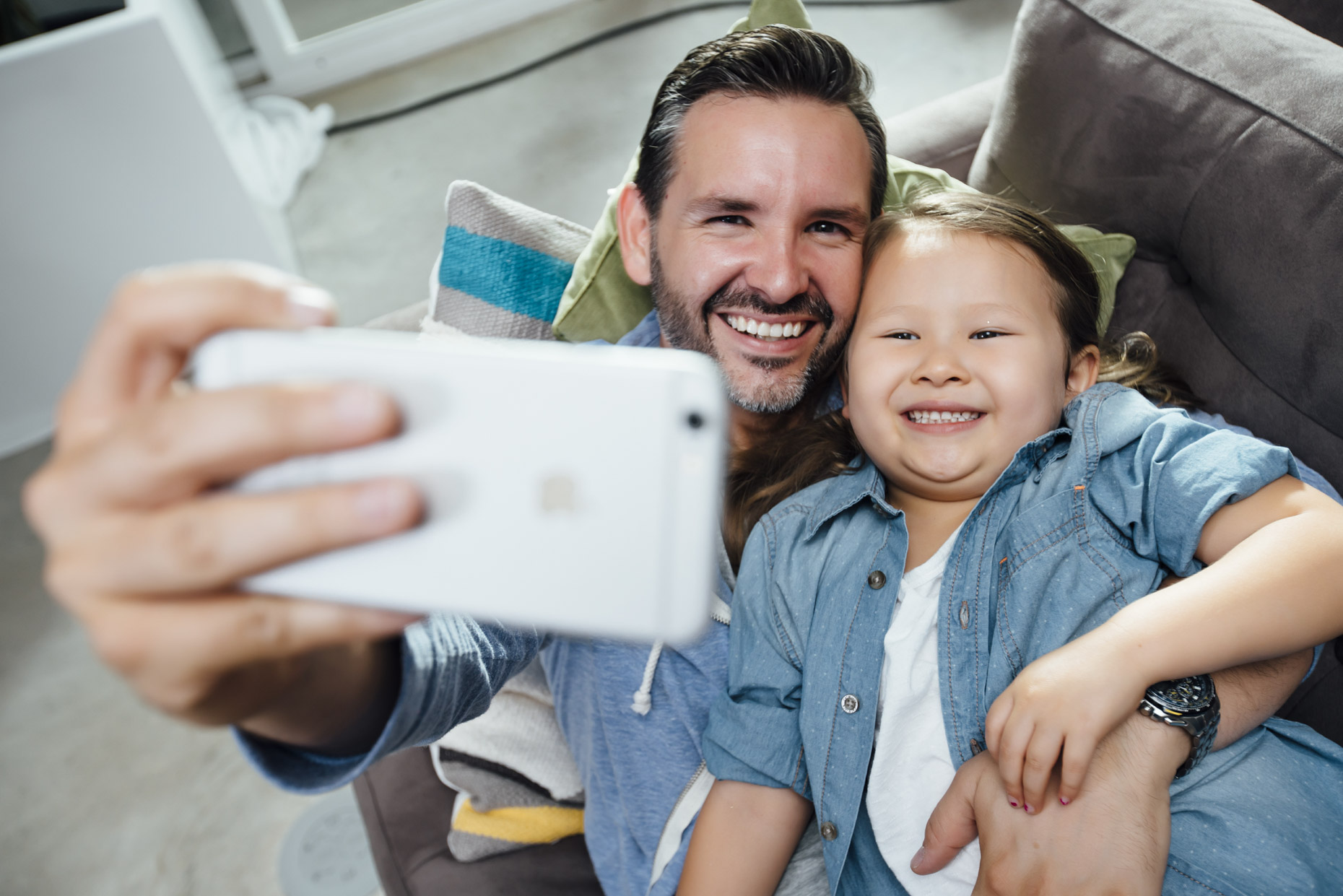 Dad taking cell phone selfie with daughter
