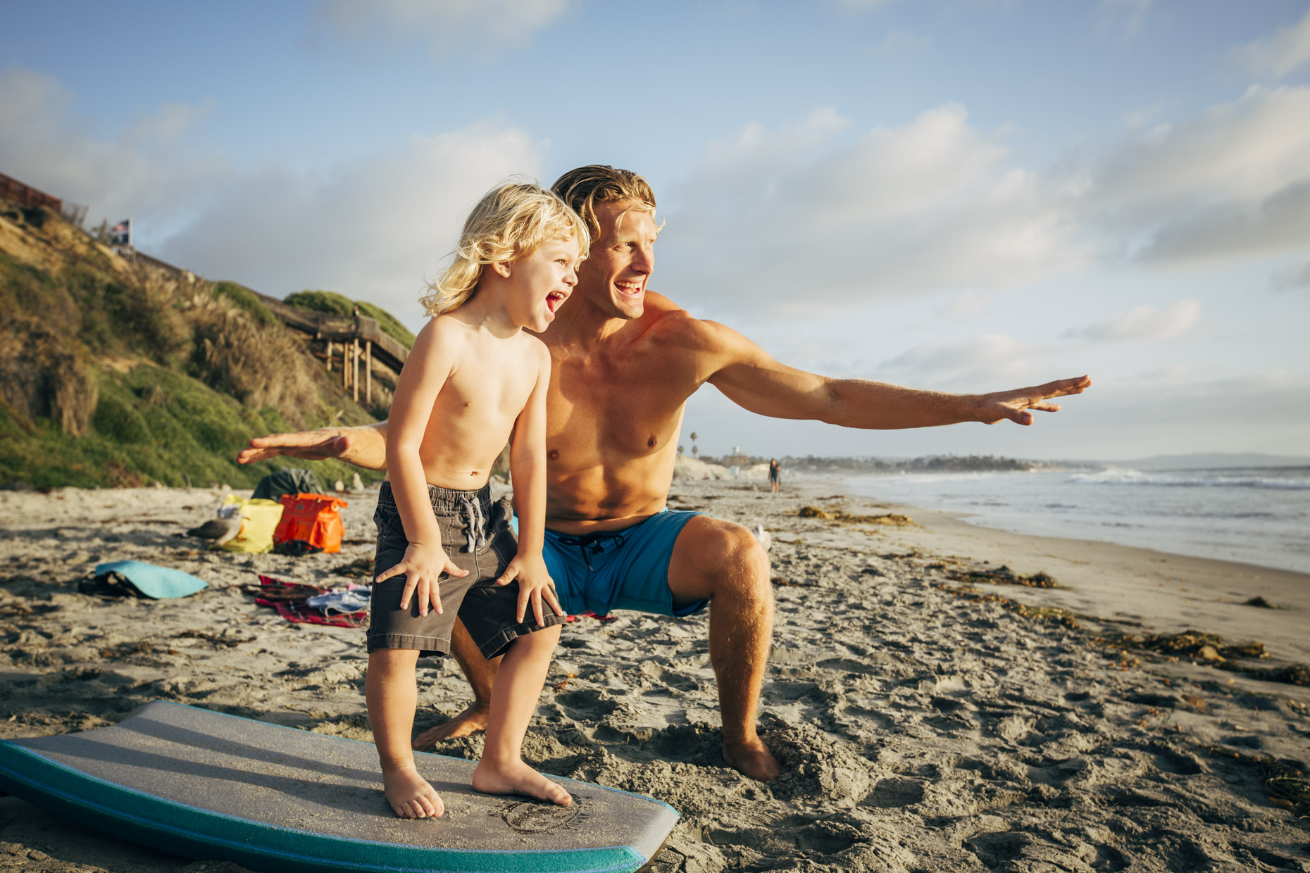 Dad teaching son how to surf on beach