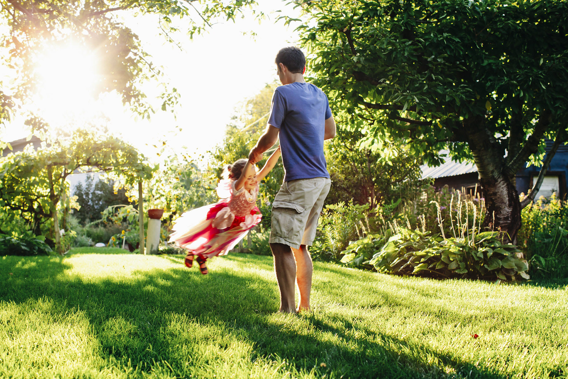 Dad twiriling daughter in fairy costume in garden