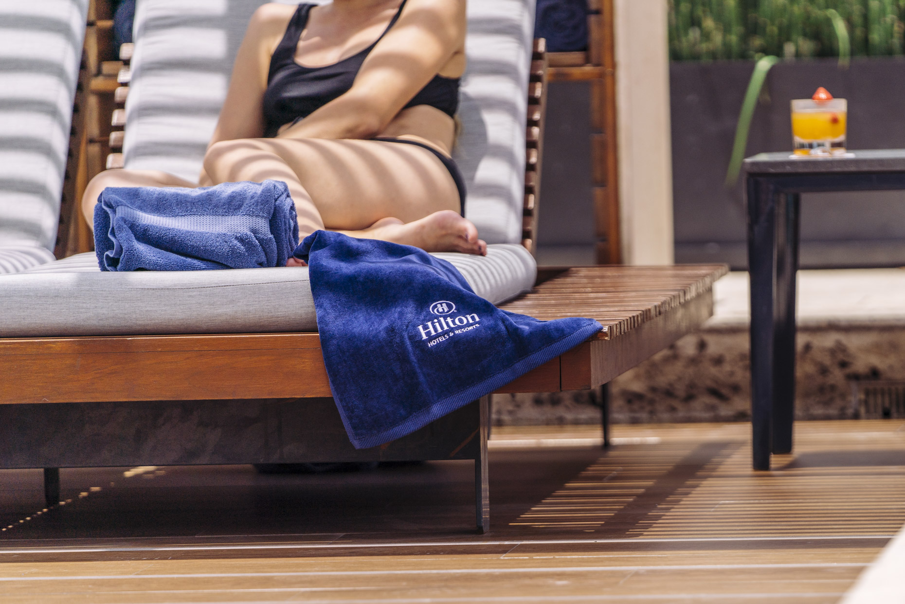 Detail shot of Hilton towel on pool lounger with woman sun bathing