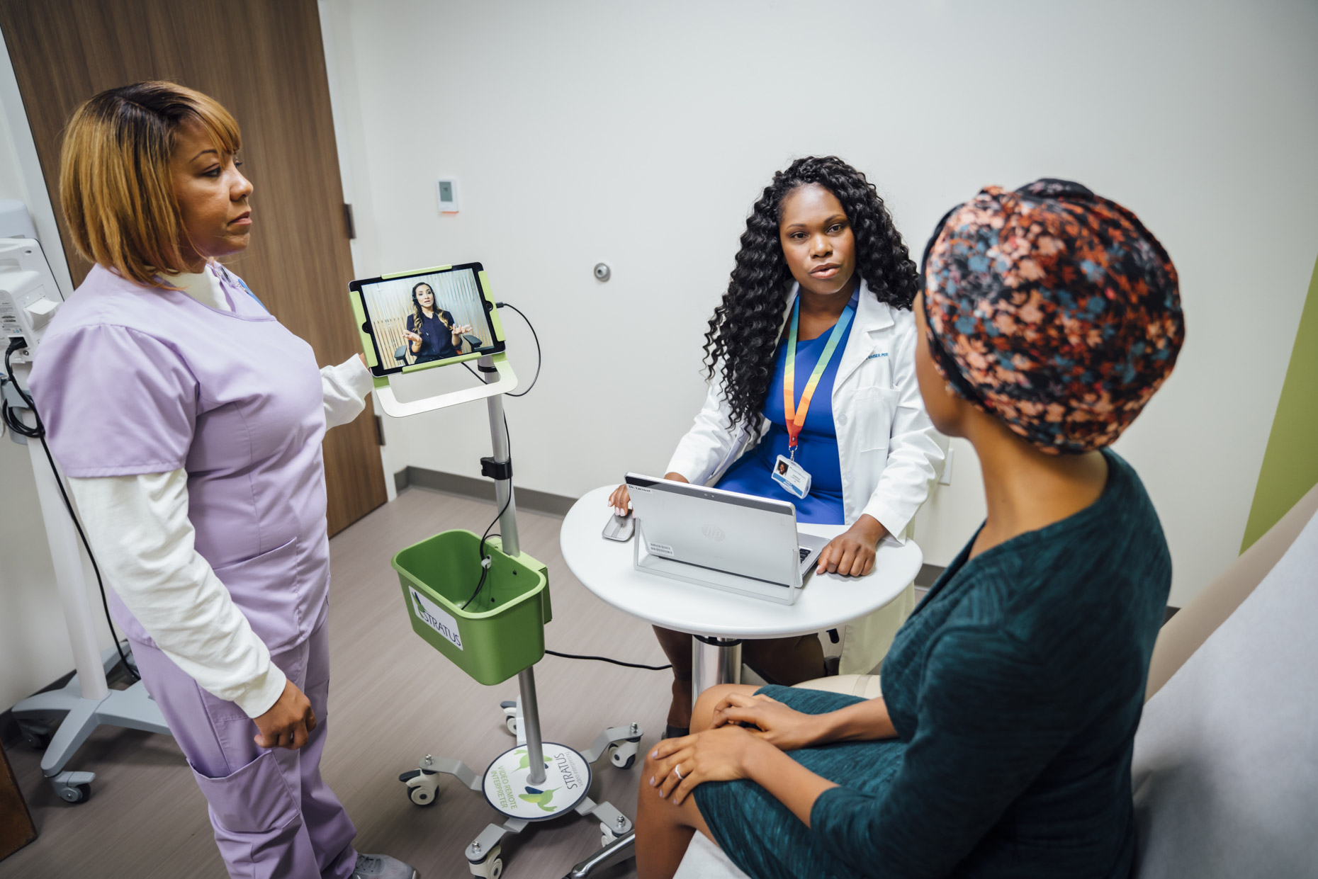Doctor and nurse talking with patient using remote translator