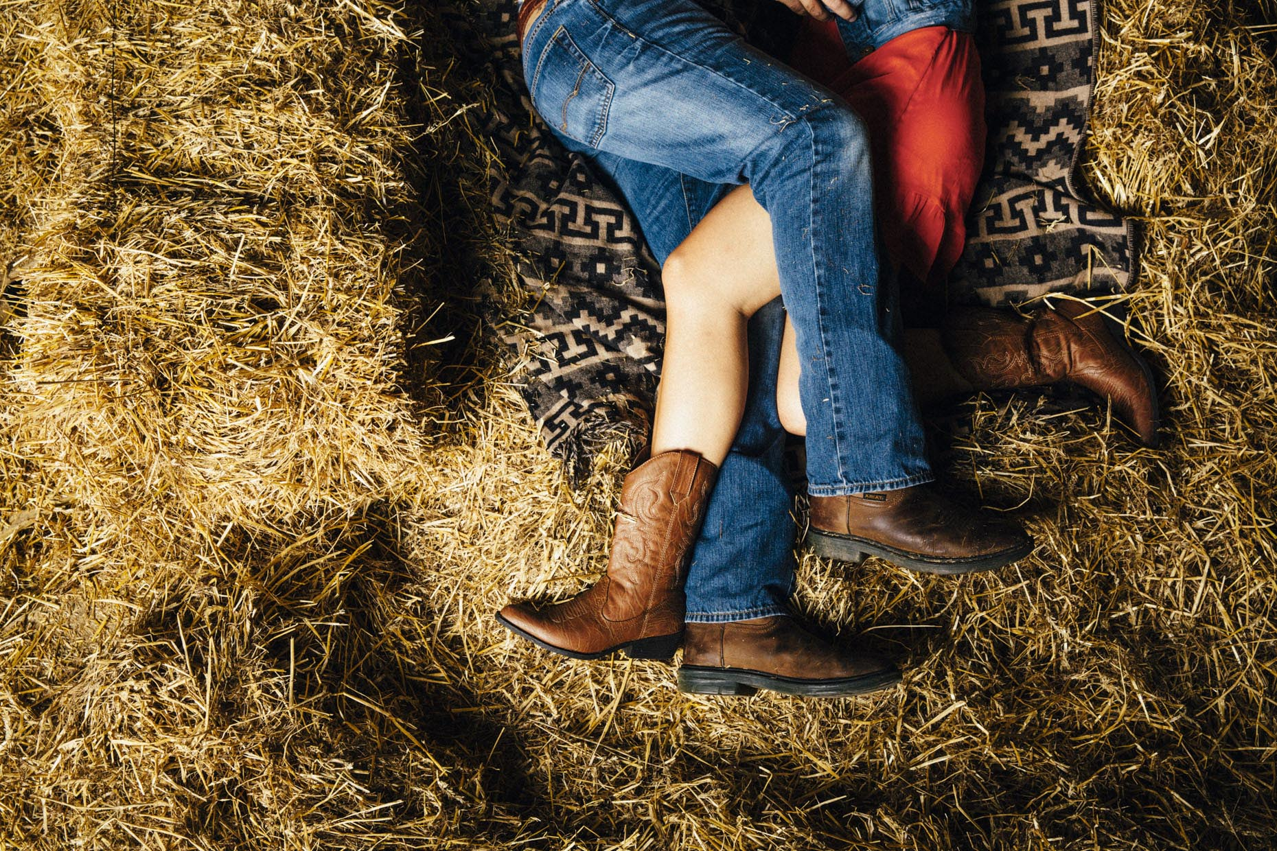 Entwined legs of couple making out in hay barn