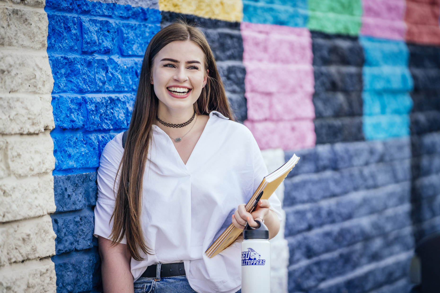 Female college student standing in front of wall holding books and laughing