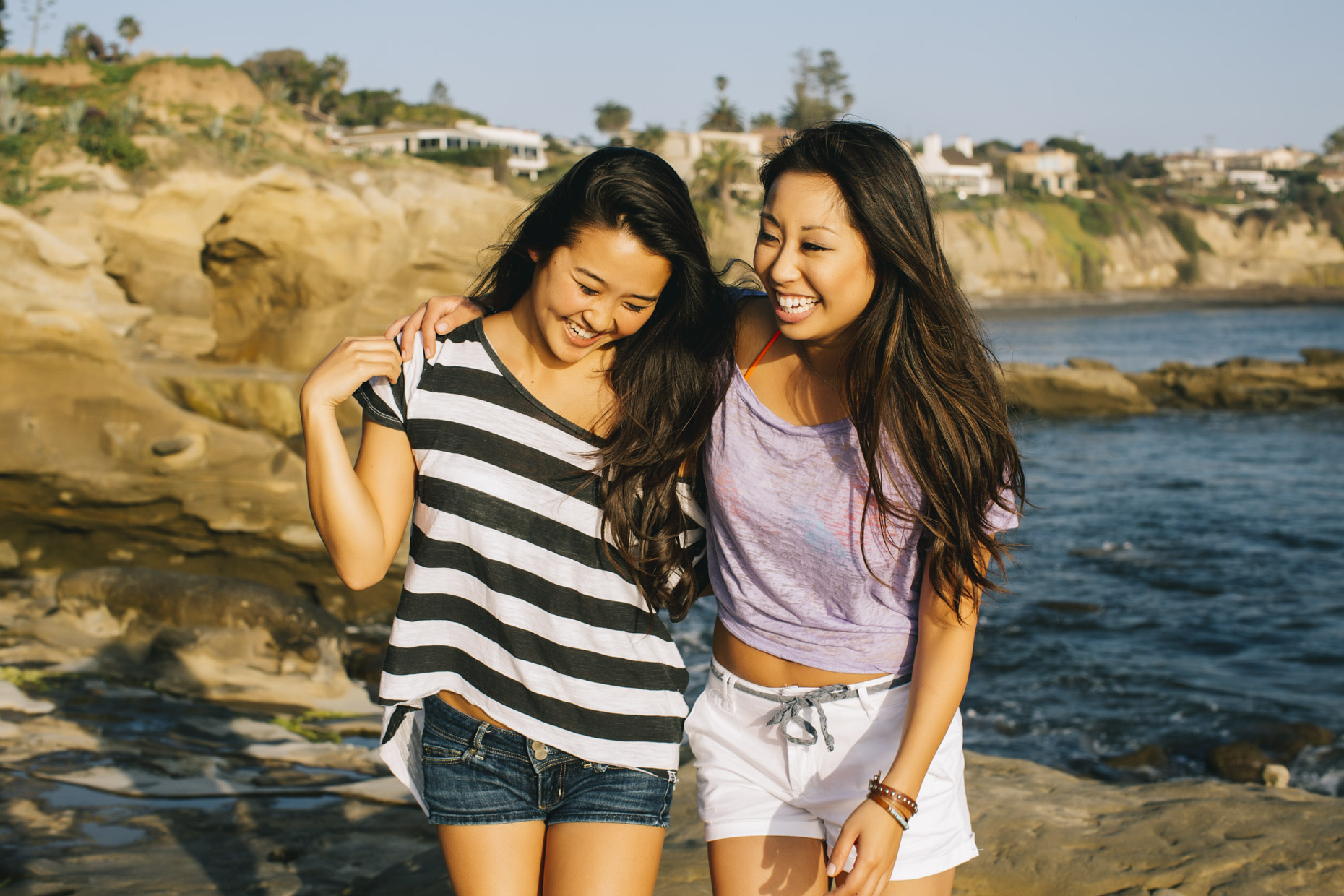 Female friends hugging and laughing at beach