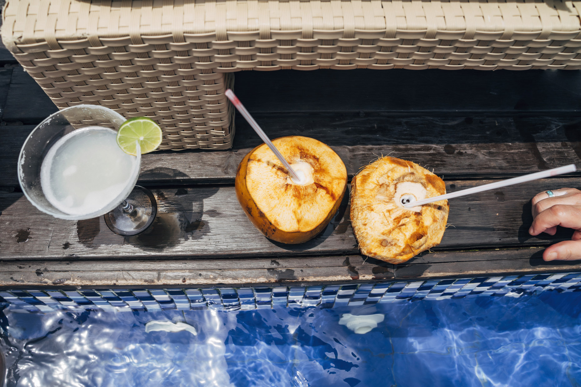 Fresh coconuts with straws and margarita cocktail poolside