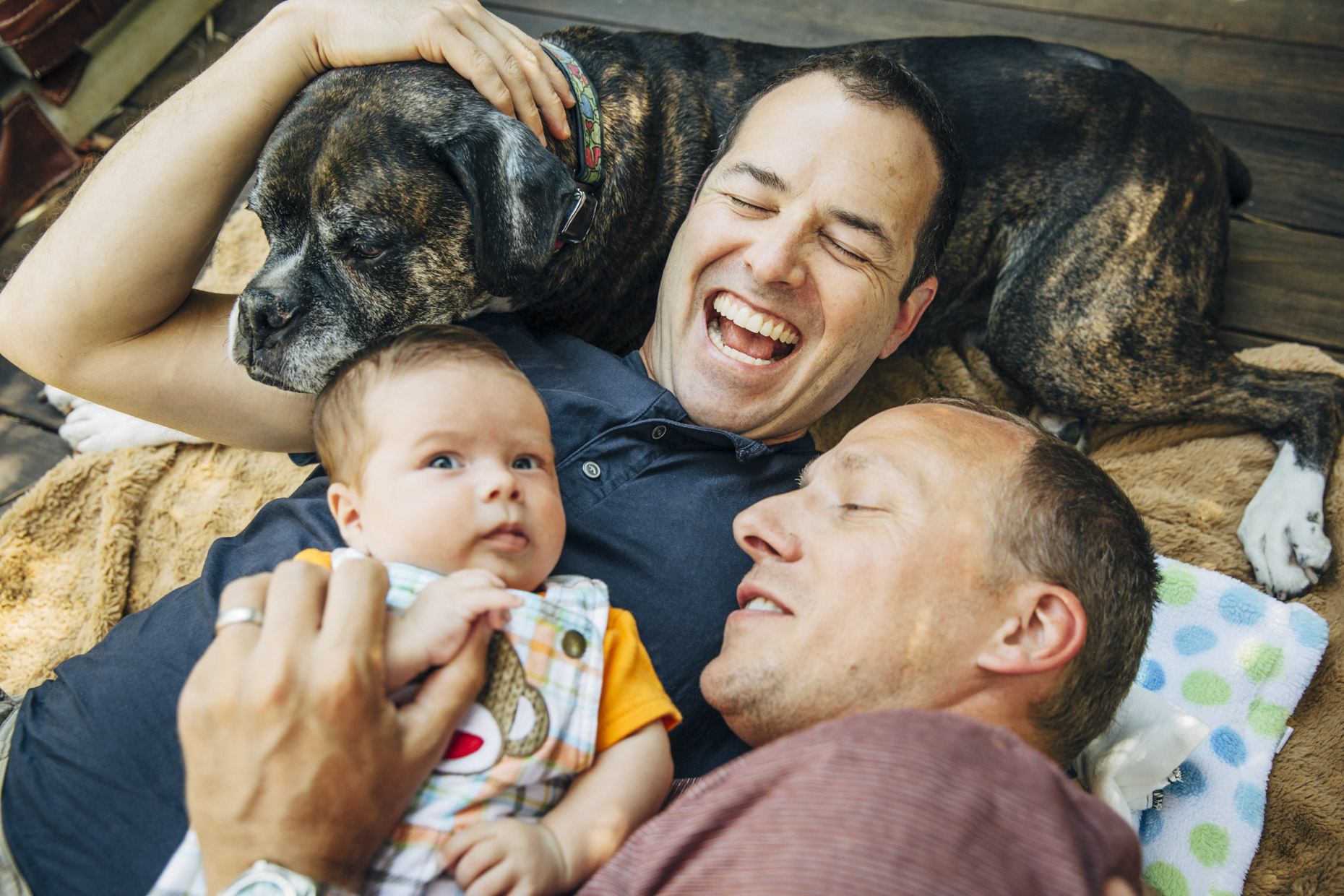 Gay-dads-snuggling-dog-baby--Inti-St-Clair-Lifestyle-is2014080300808