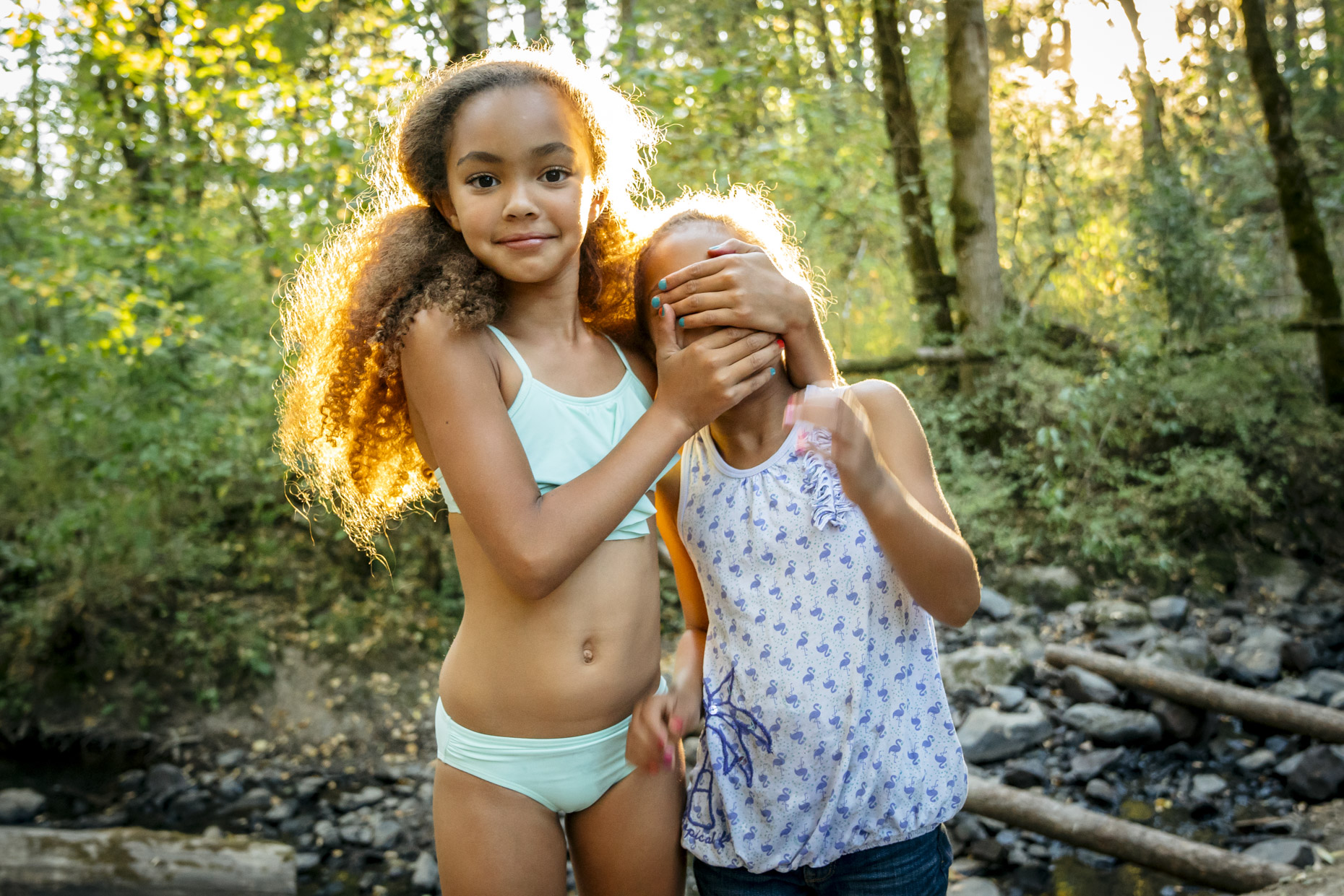 Girl with hands covering sisters eyes standing next to creek in forest