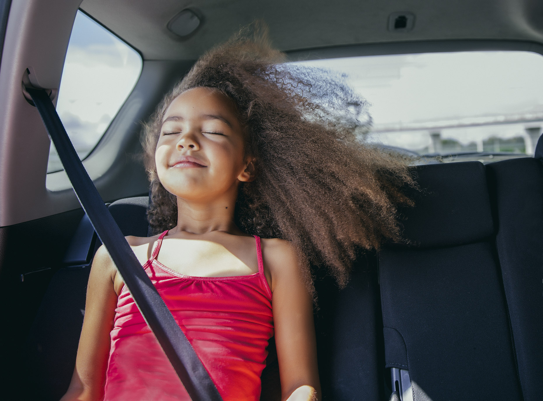 Girl in car with eyes closed and hair blowing in the wind