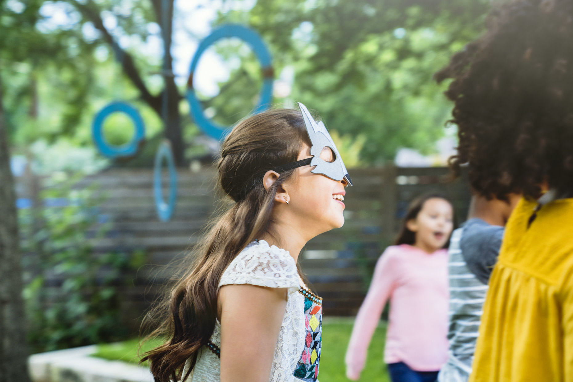 Girl in mask running in back yard with friends