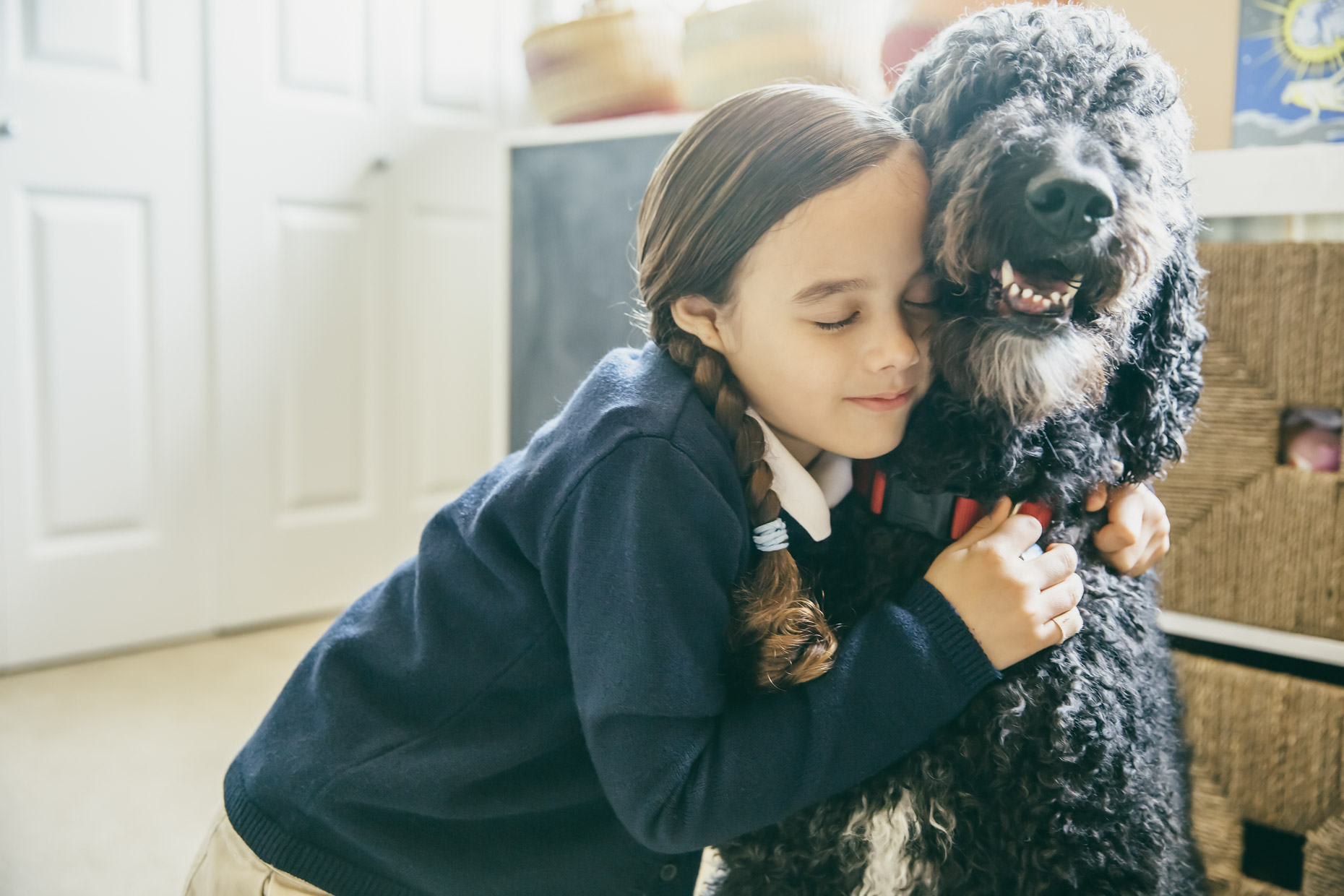 Girl in school uniform hugging labradoodle dog