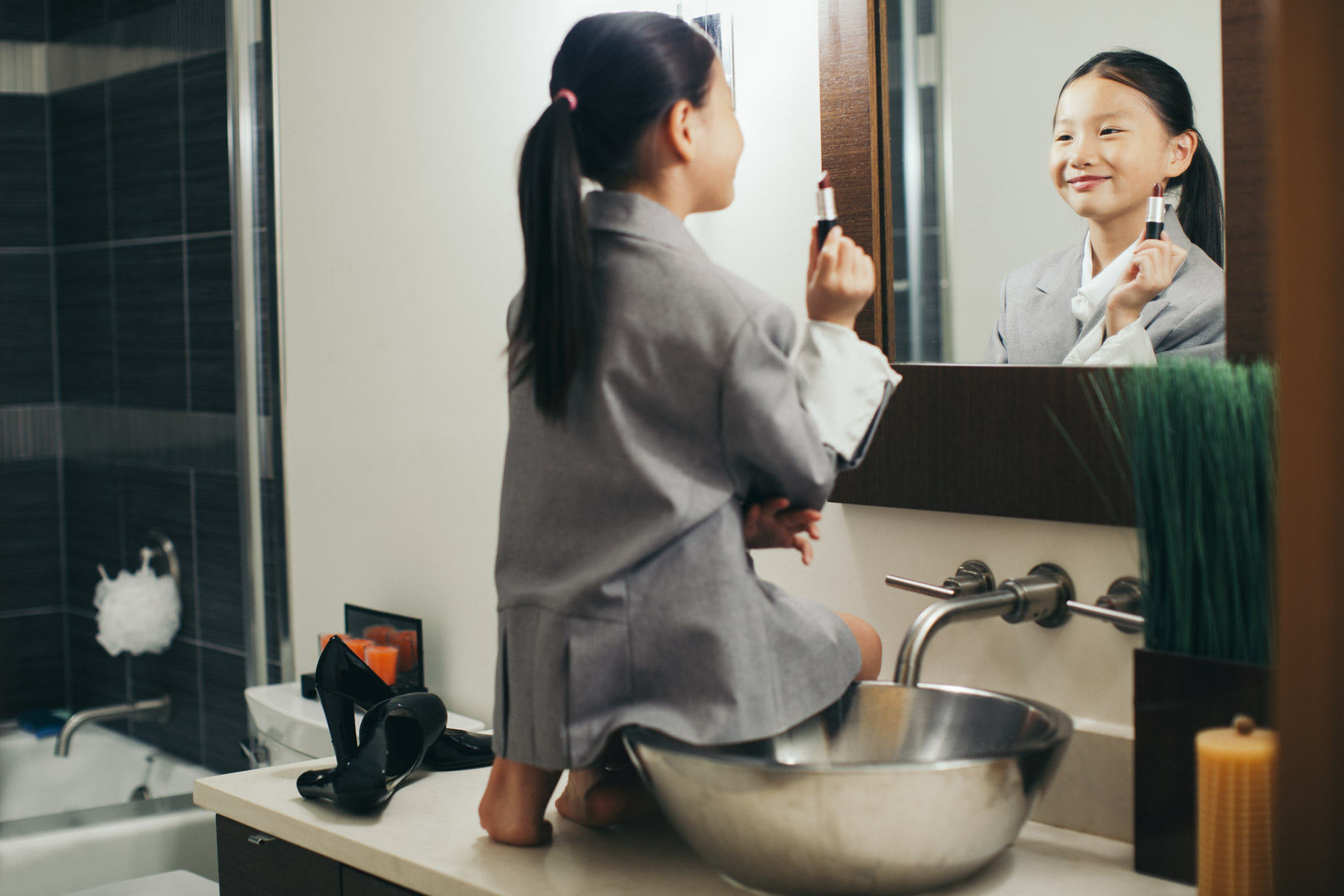 Asian girl in suit jacket on bathroom counter trying on lipstick in front of mirror