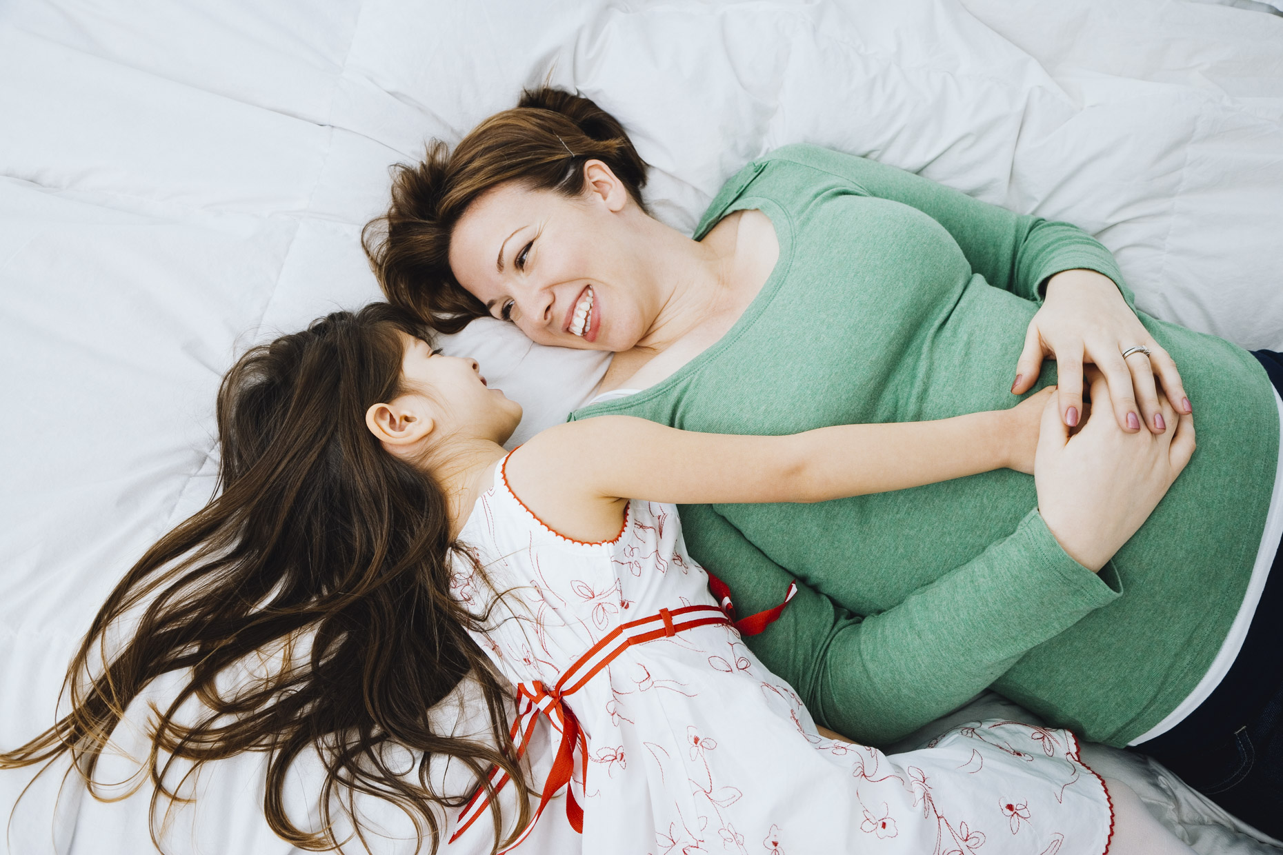 Girl-laying-on-bed-with-pregnant-mom-touching-belly-Inti-St-Clair-20071218168copy