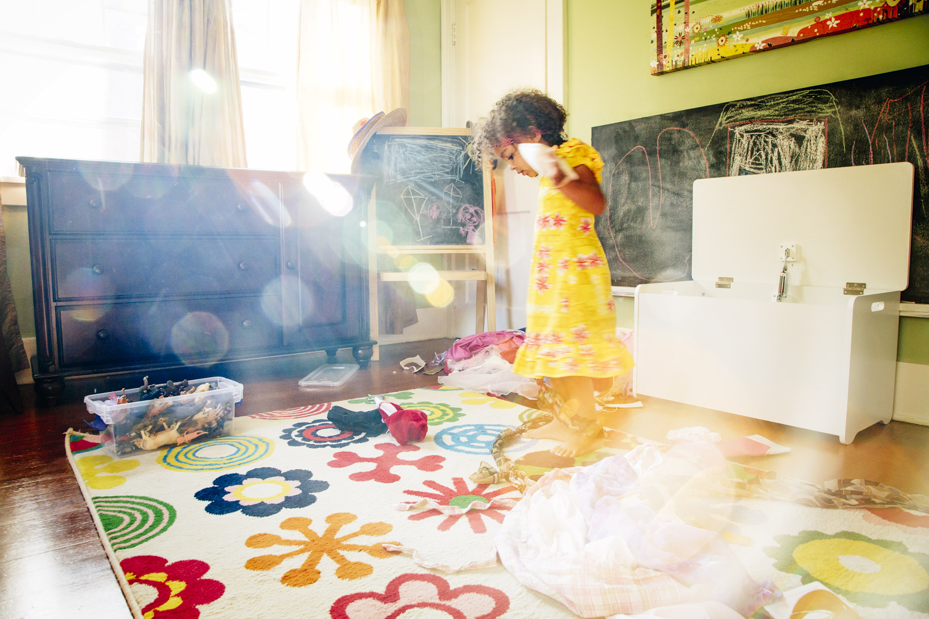 Girl playing dress-up in sunlight filled bedroom