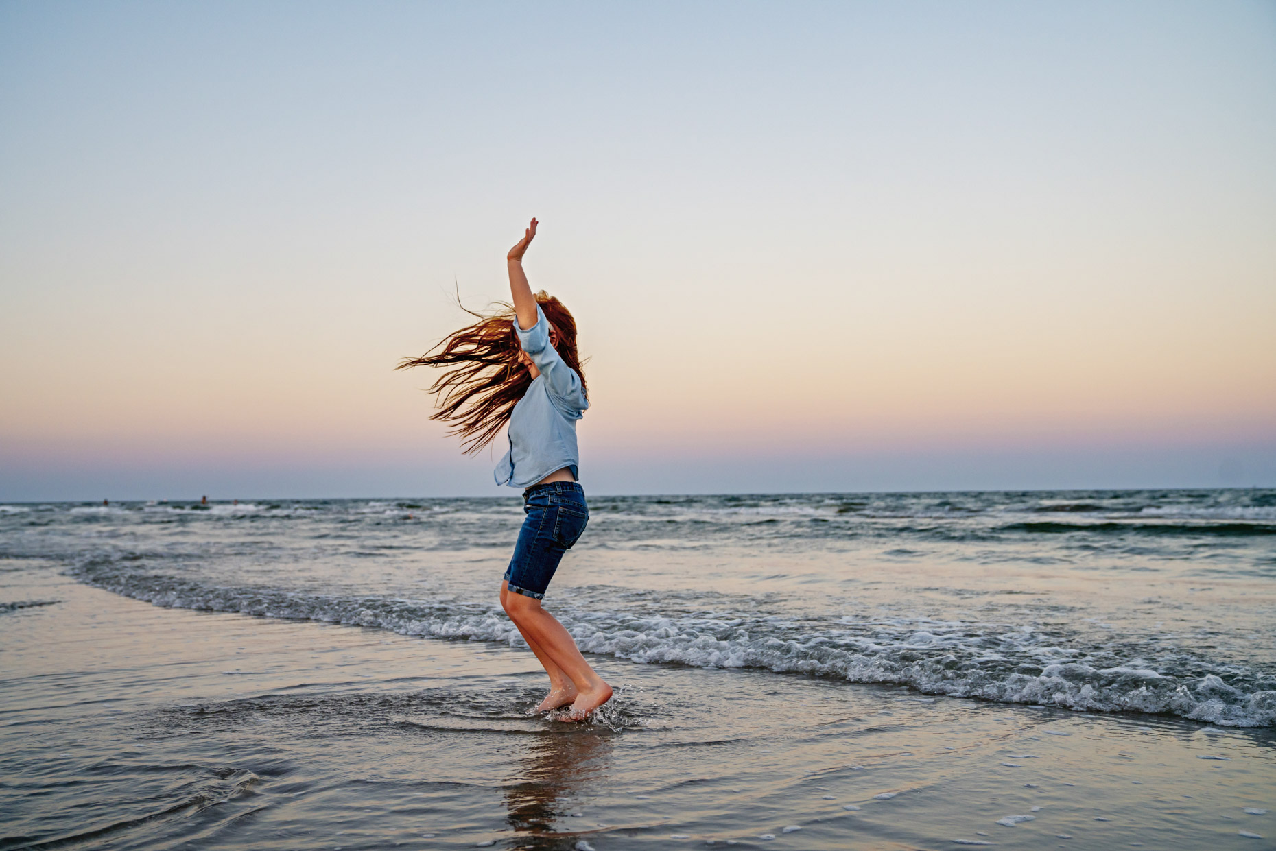 Girl with long red hair jumping in the waves on beach at sunset