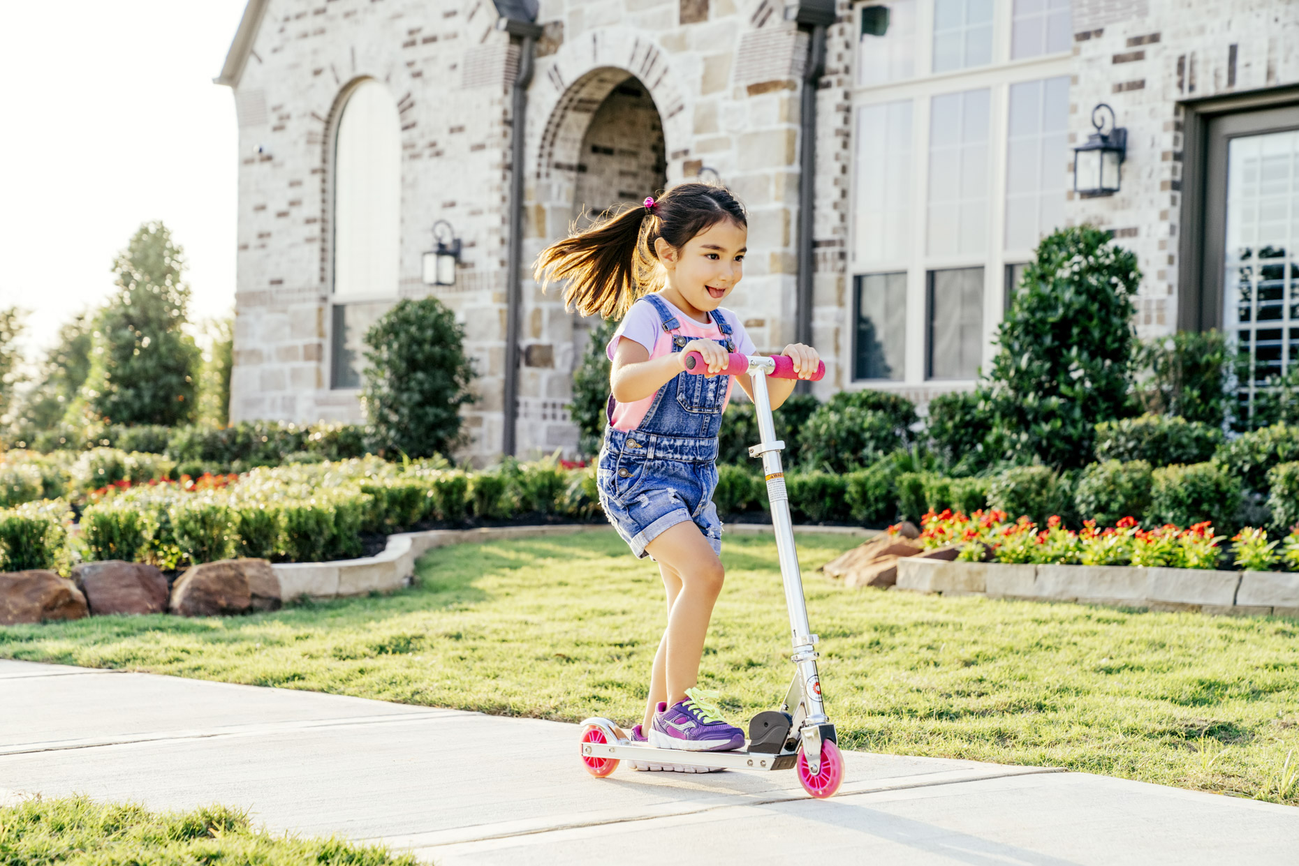Girl riding scooter on sidewalk in front of house