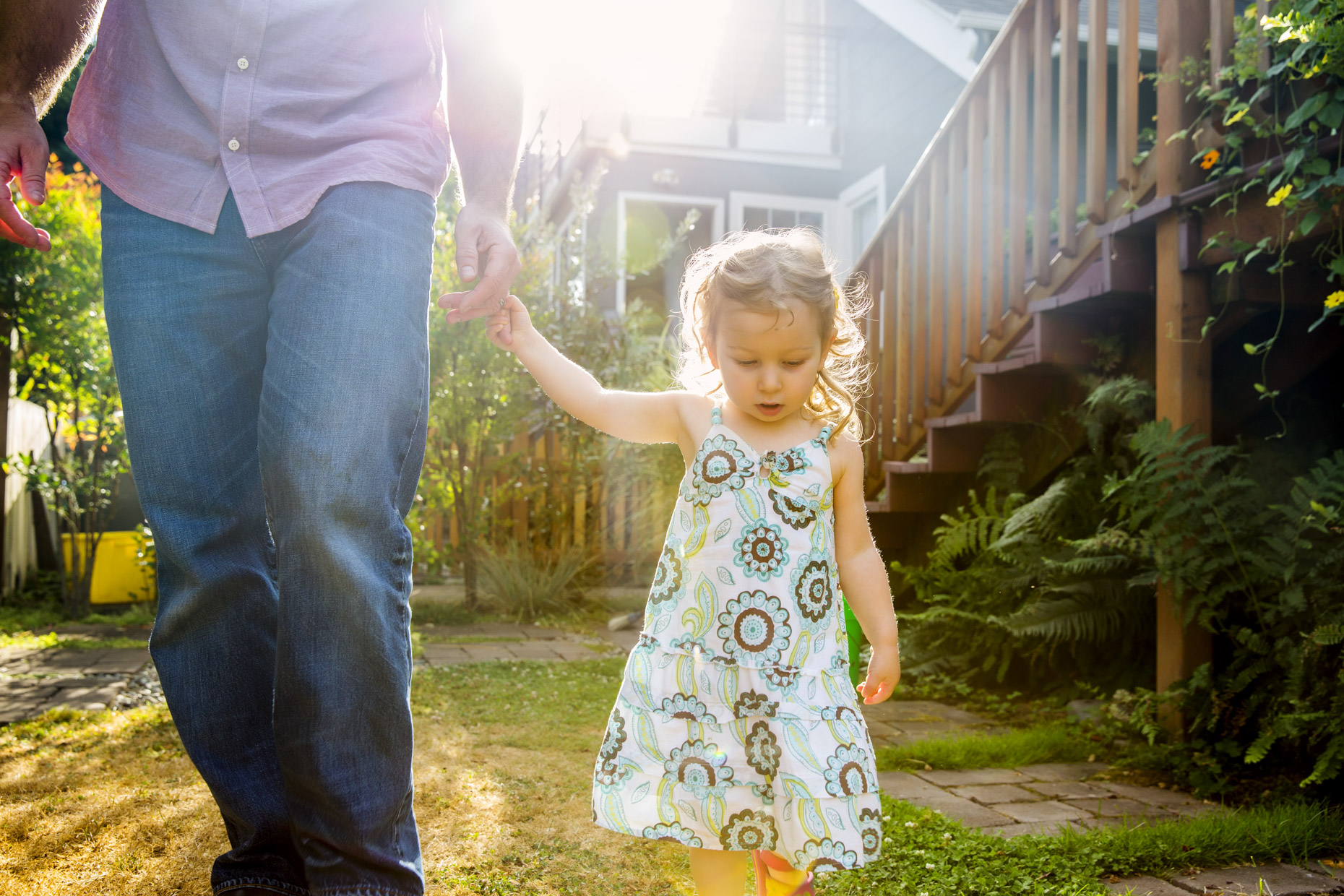 Girl walking in sunny garden holding dad