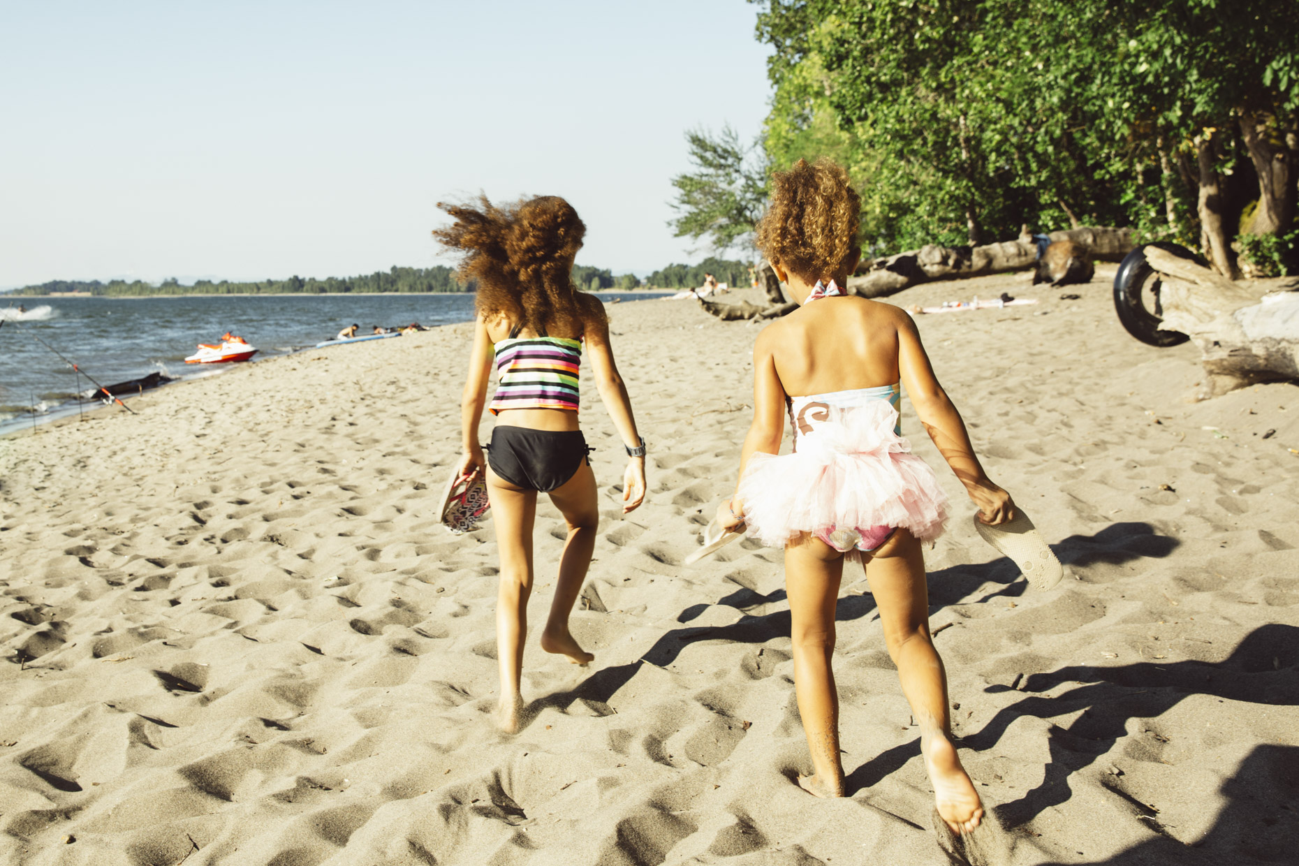 Girls in swimsuits and tutu running on beach