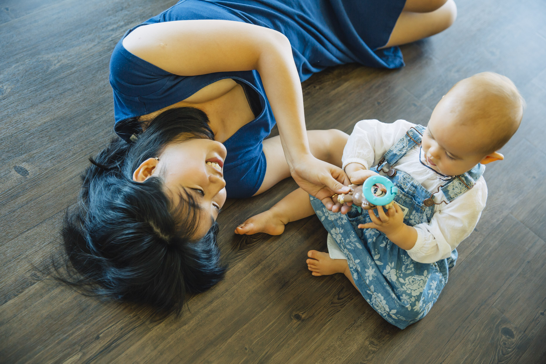Happy asian woman laying on floor playing with her baby