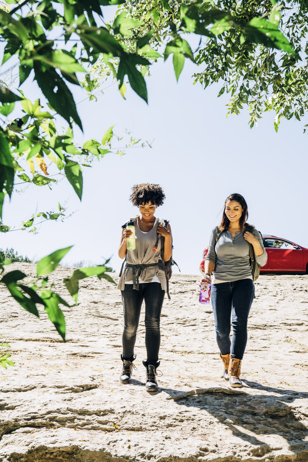 Happy female friends walking away from car to hike