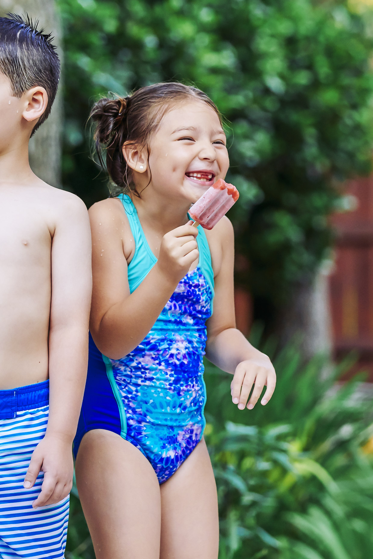 Happy-girl-in-swimsuit-eating-popsicle-John_House_Pool_0670