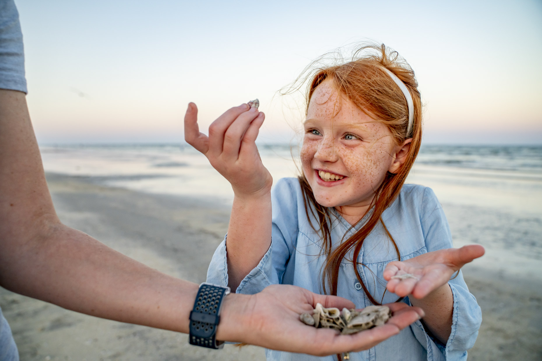 Happy girl looking at sea shells from mom