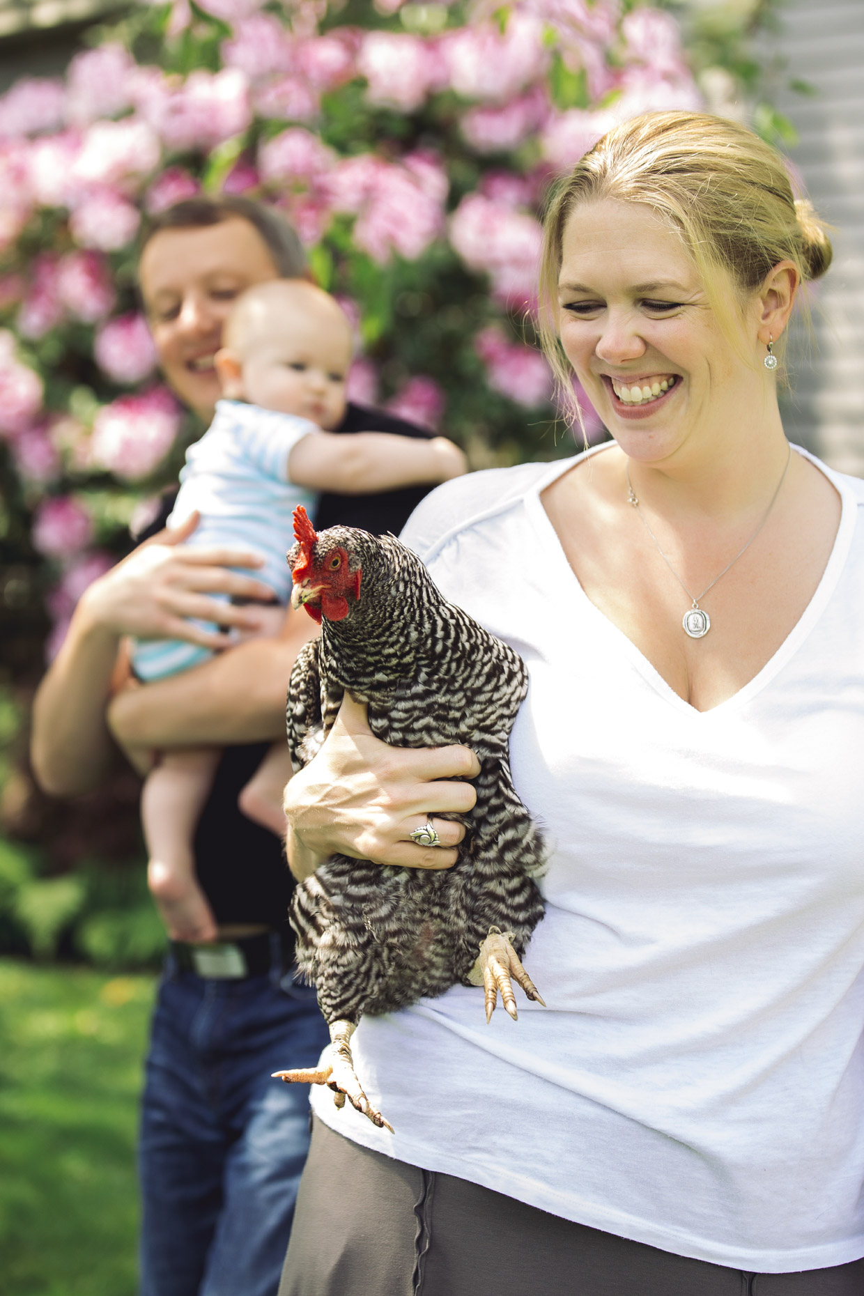 Happy woman holding chicken in garden with mand and baby walking behind