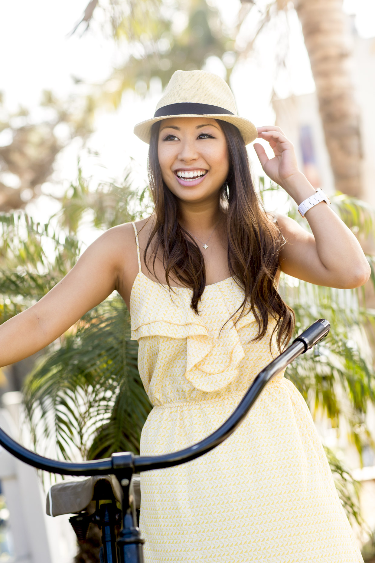 Happy woman in yellow dress and hat with bicycle