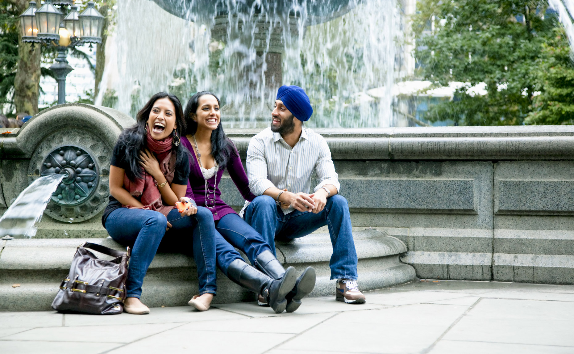 Indian-friends-sitting-by-fountain-in-park-laughing-Inti-St-Clair-Lifestyle-is200909260249copy