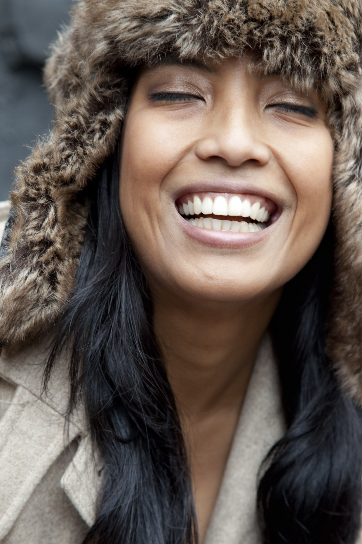 Inti St Clair portrait of Indian woman in fur hat laughing with eyes closed