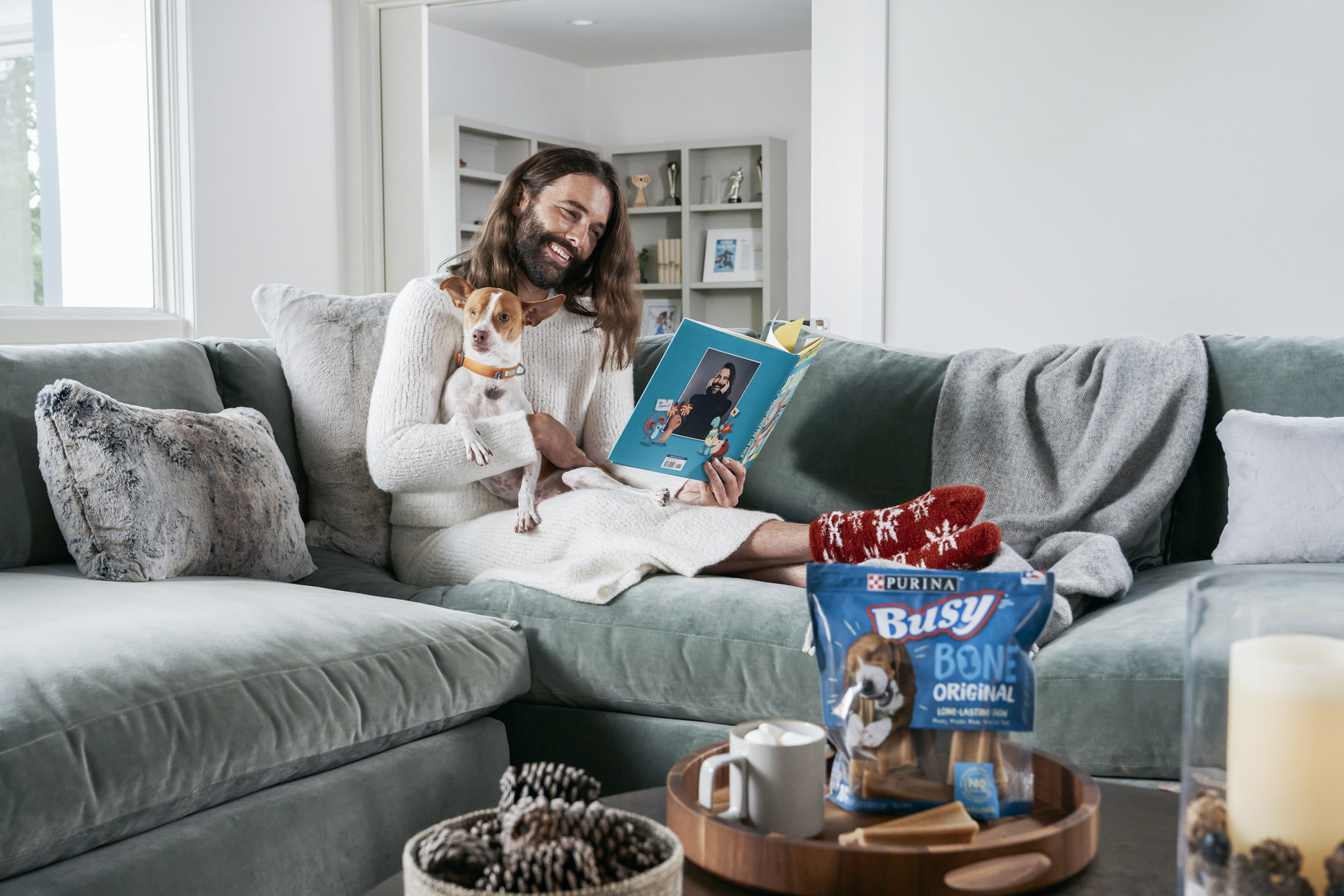 Jonathan Van Ness pet dog Pablo on couch with Purina Busy Bone treat reading book