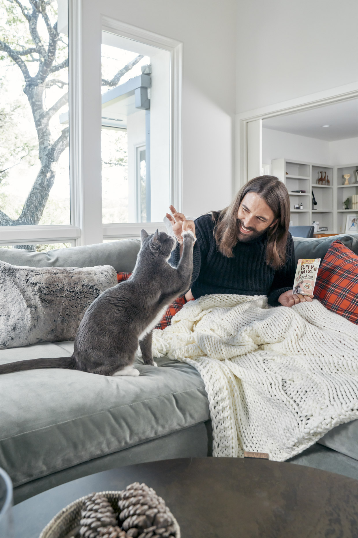 Jonathan Van Ness feeding cat Purina Friskies party mix treat on sofa
